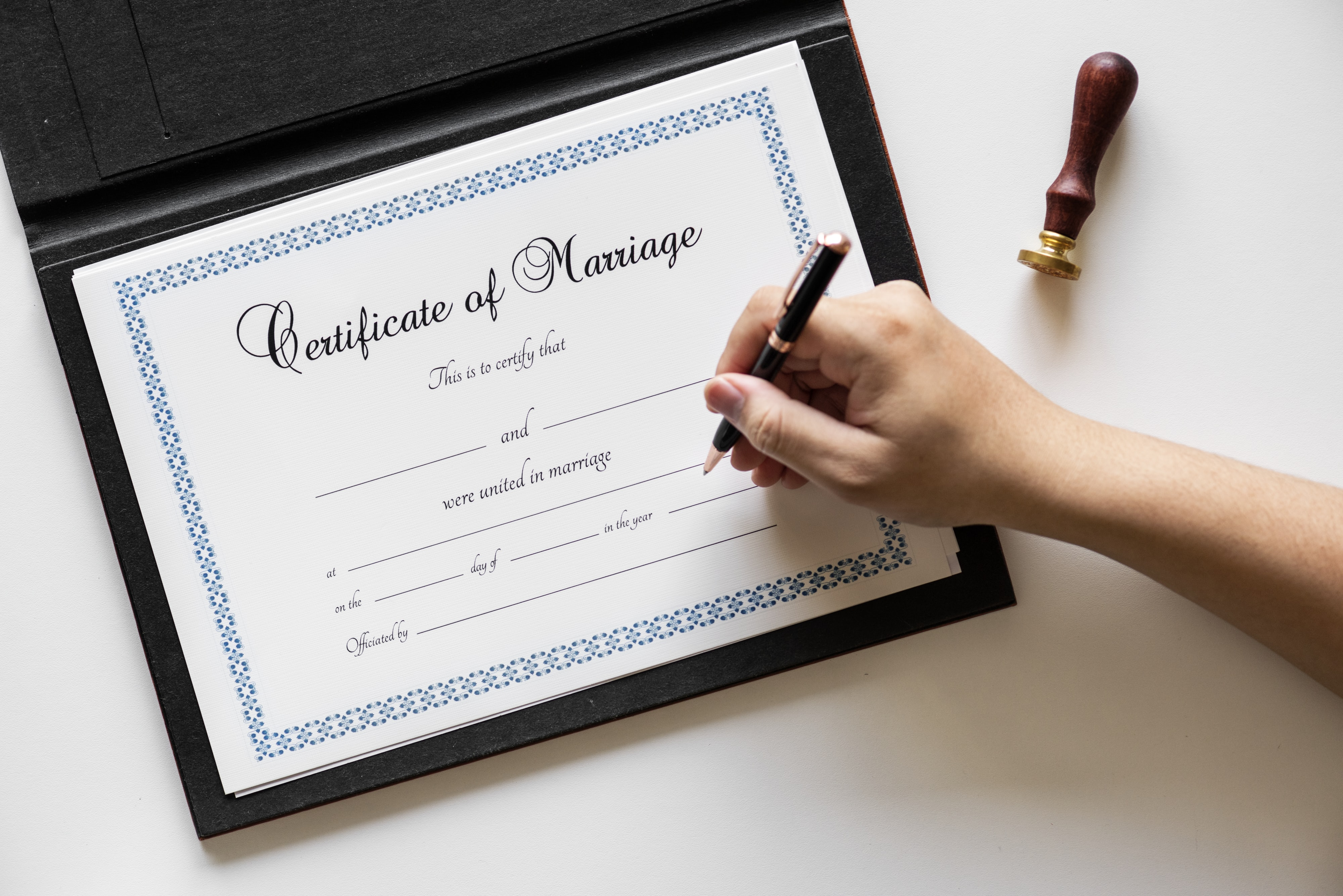person writing on marriage certificate