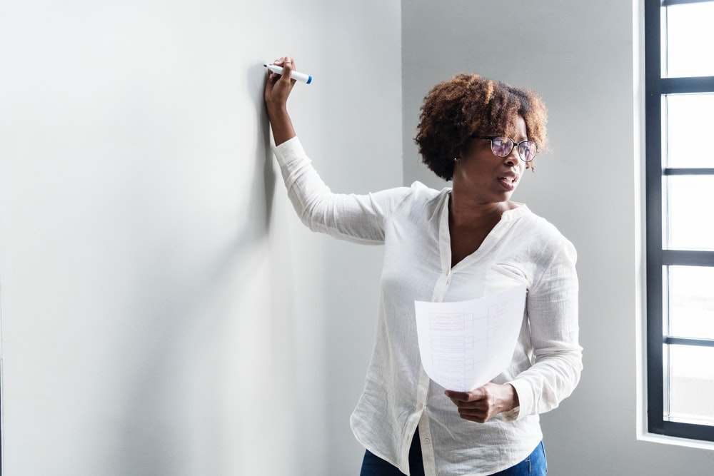 woman writing on whiteboard holding white printer paper