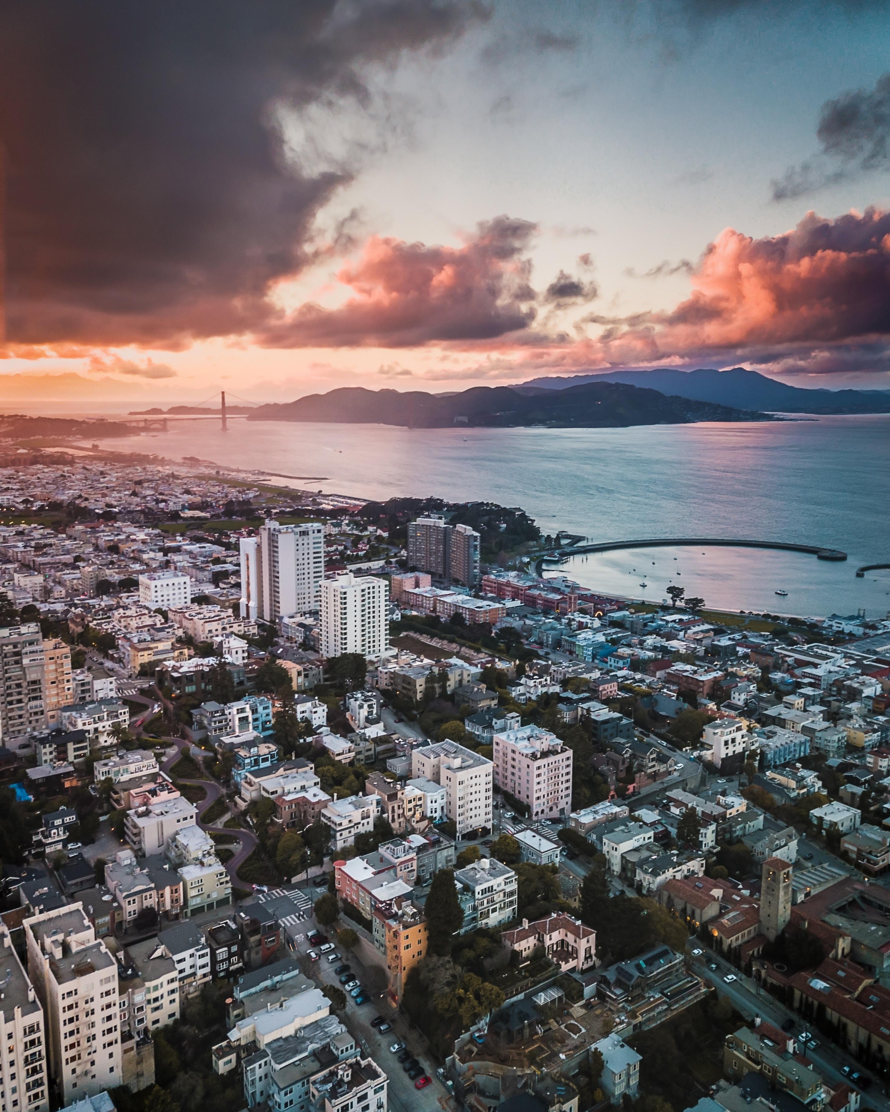 aerial photography city near sea under golden sky