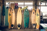 six assorted-color surfboards on brown board