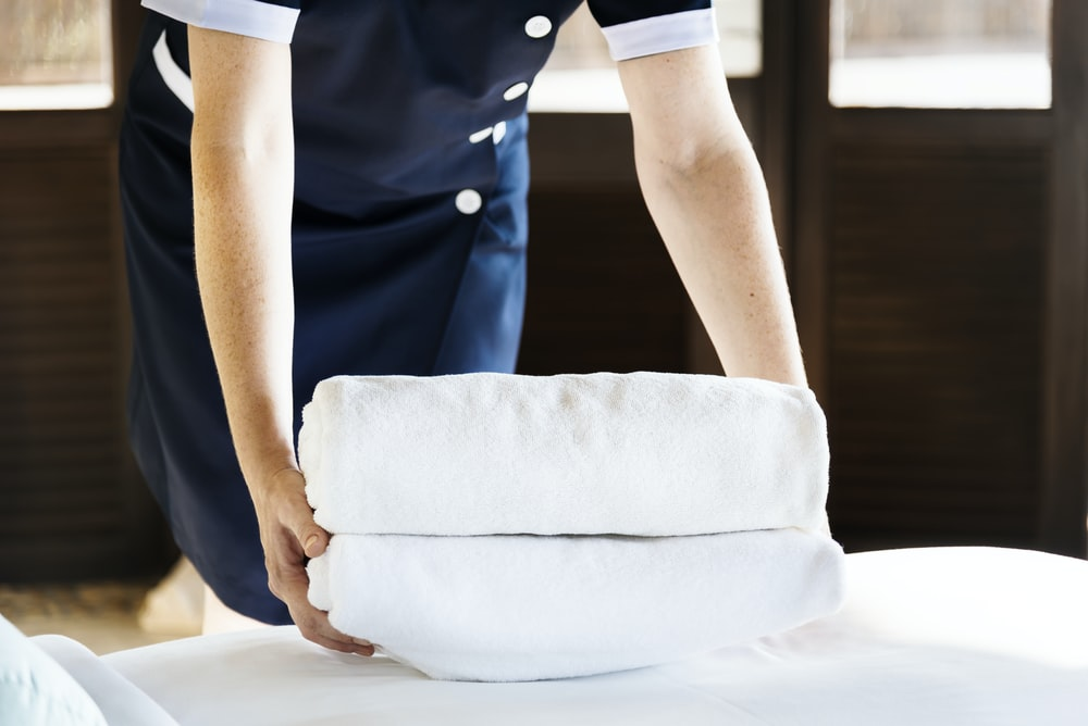 person holding two white towels