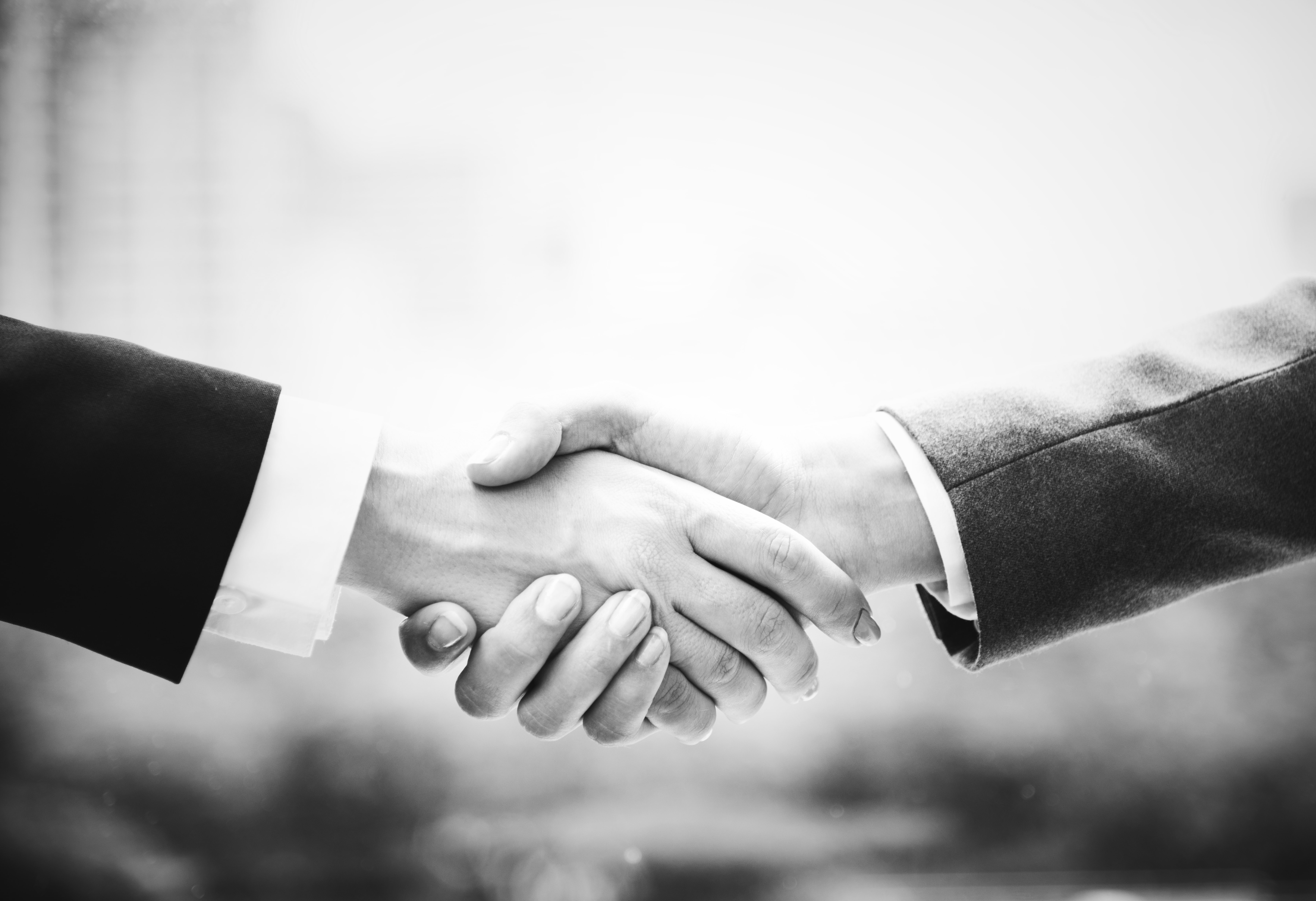 grayscale photo of two person handshakes