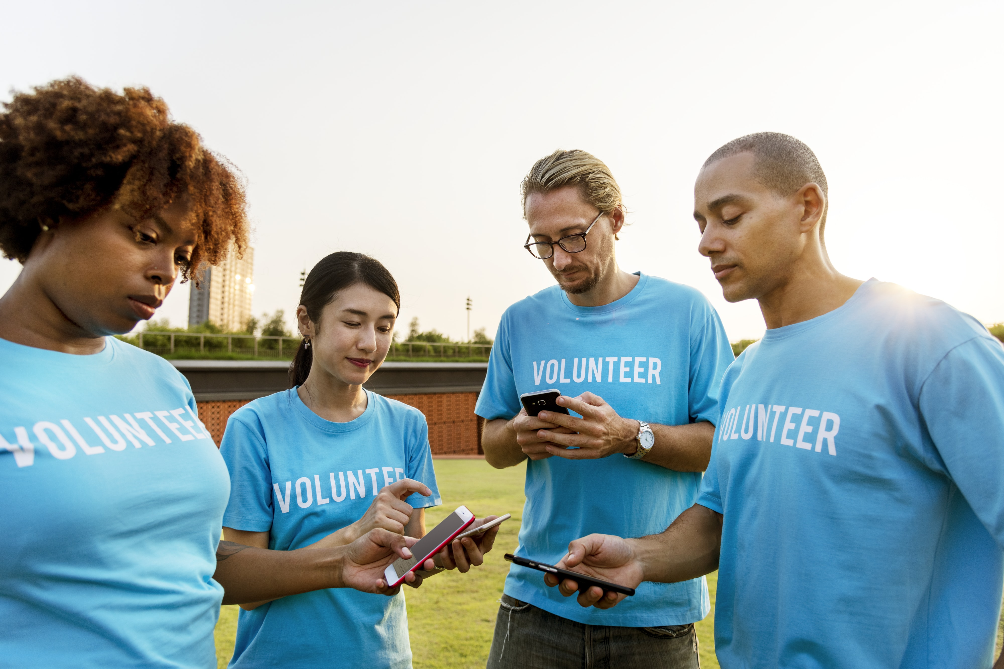 four people with Volunteer shirts standing on grass field at daytime