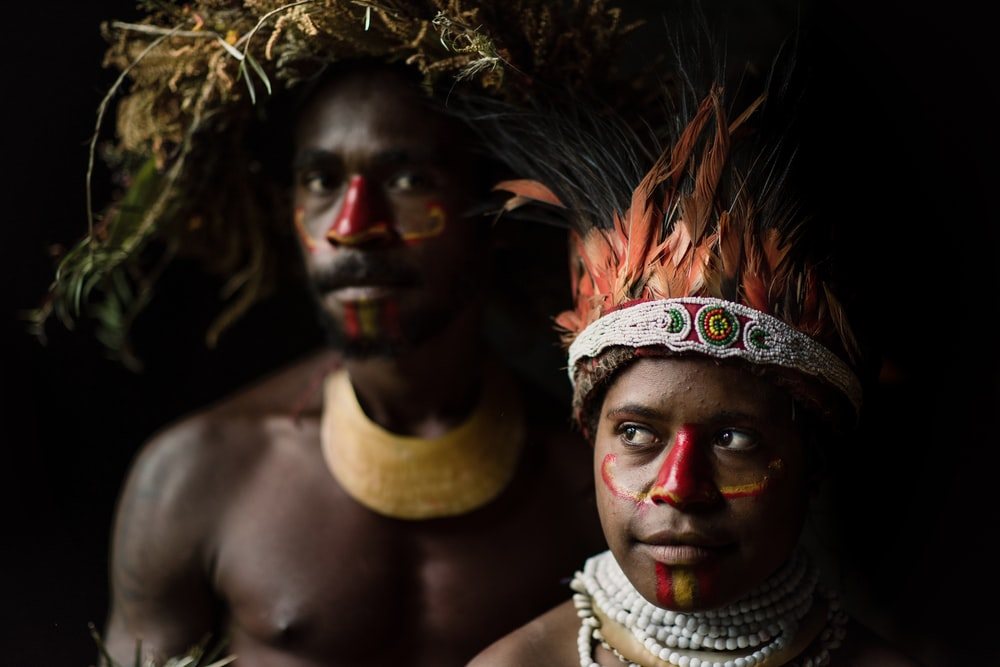 two man and woman standing beside each other while wearing headdress