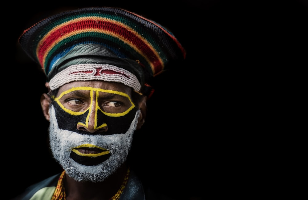 man wearing hat with face paint