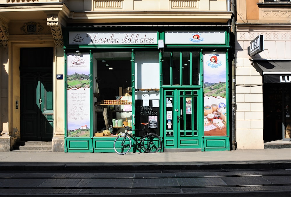 black bicycle parked in front of green store facade