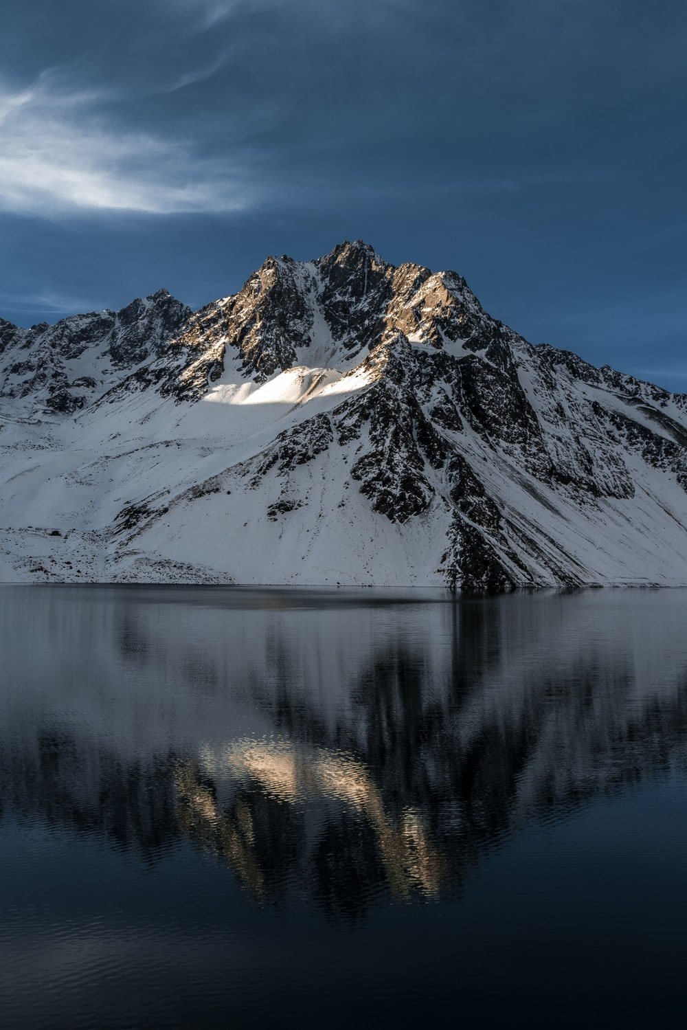 body of water near mountain coated by snow