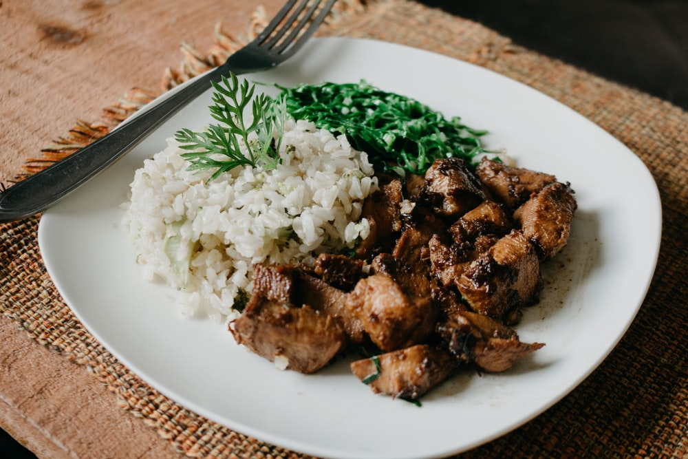 cooked meat and rice on plate