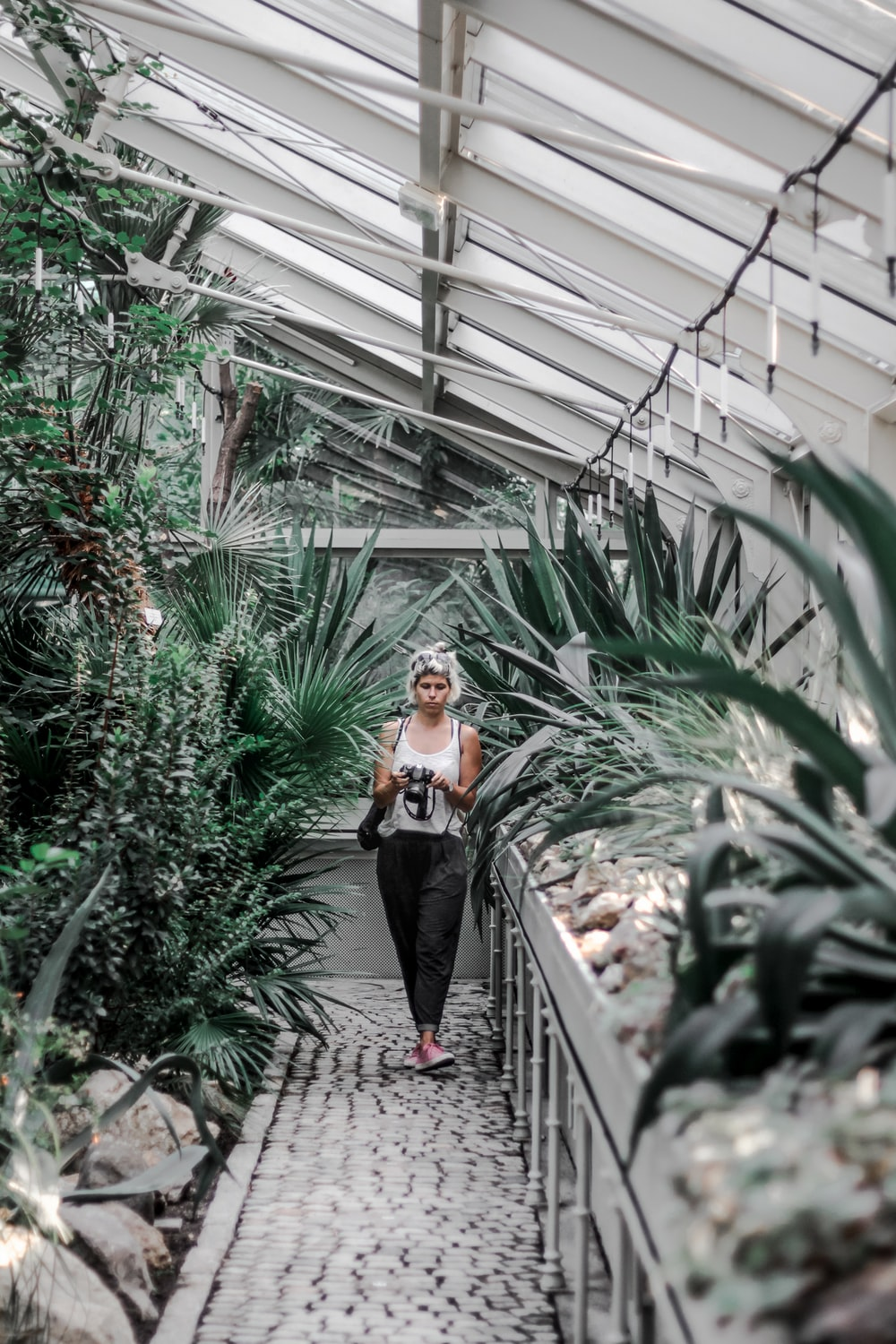 woman walking on pathway beside plants inside greenhouse