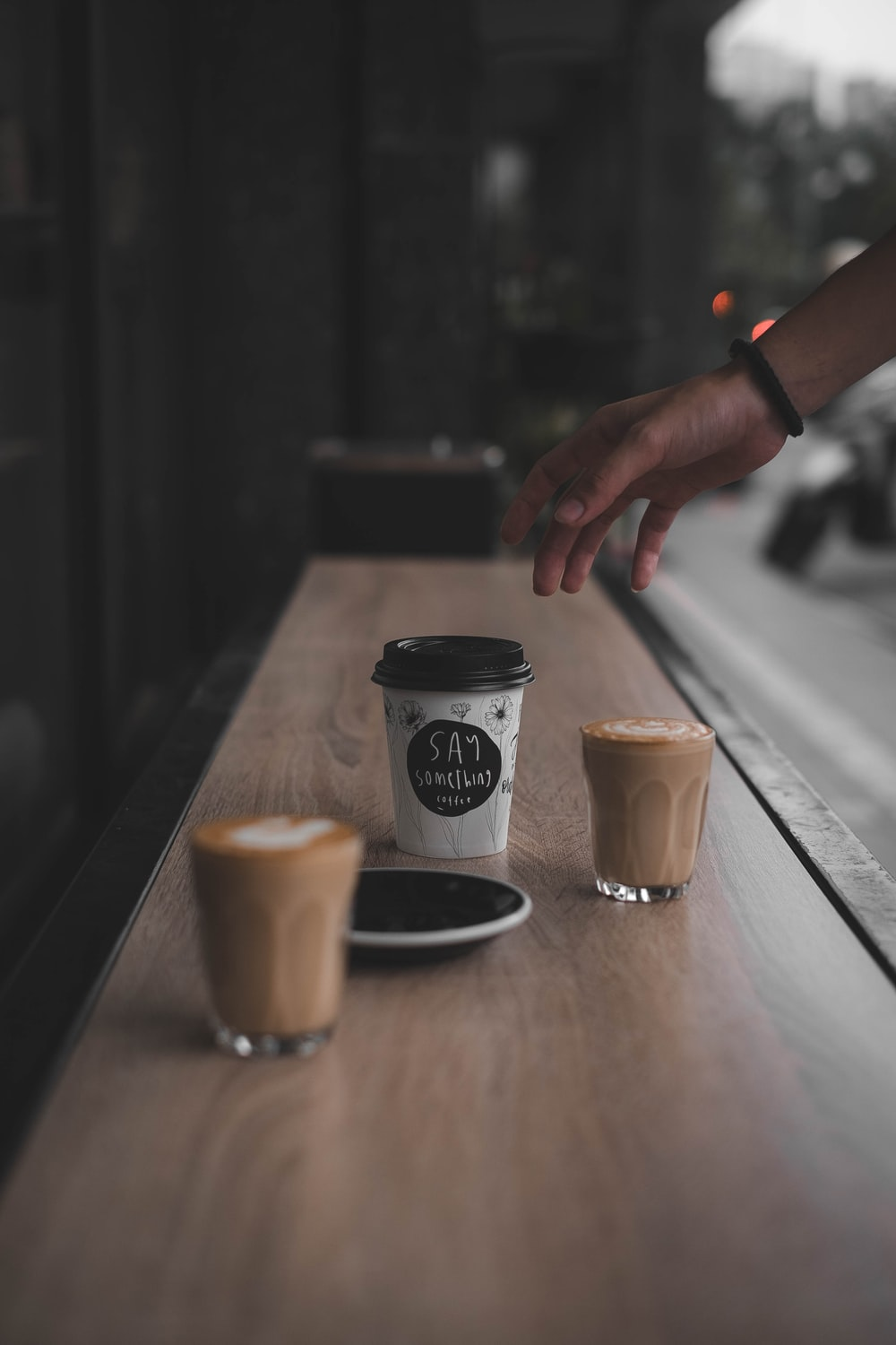 person reaching coffee cup beside glass on brown surface