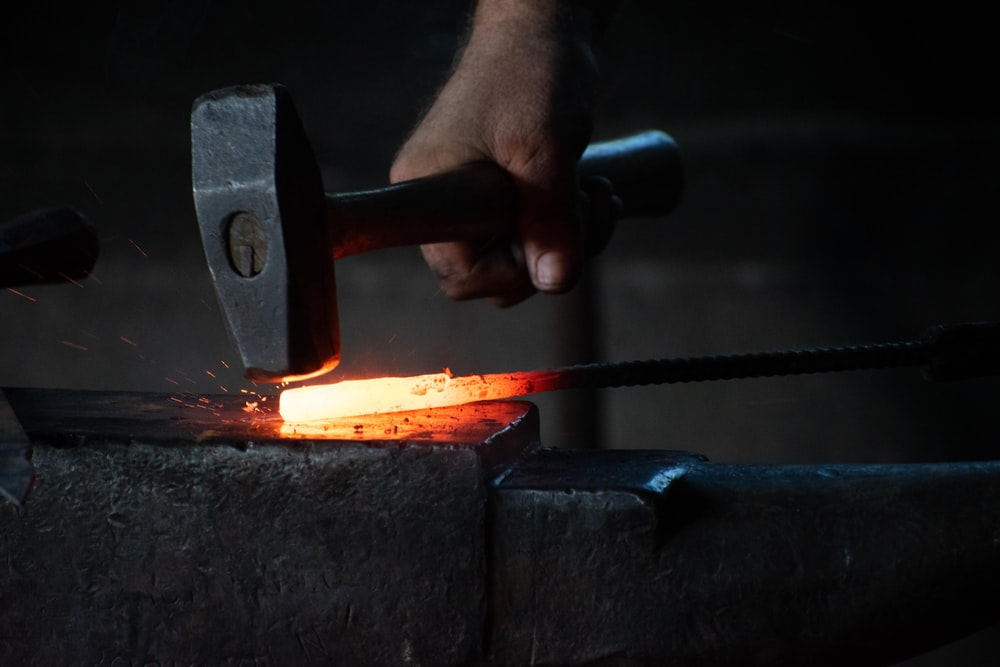 man pounding hammer on hot iron rod