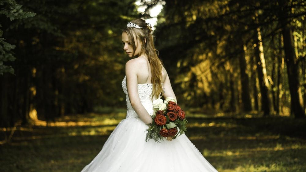 woman in wedding dress standing near trees