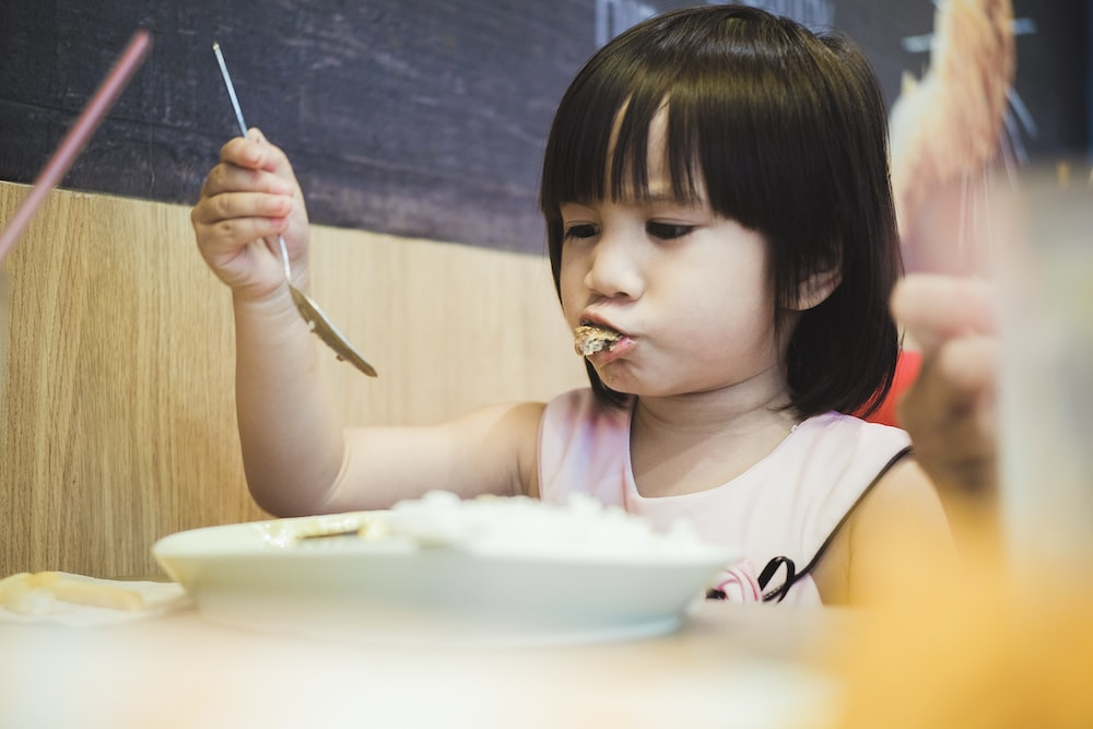 girl eating while holding spoon over plate