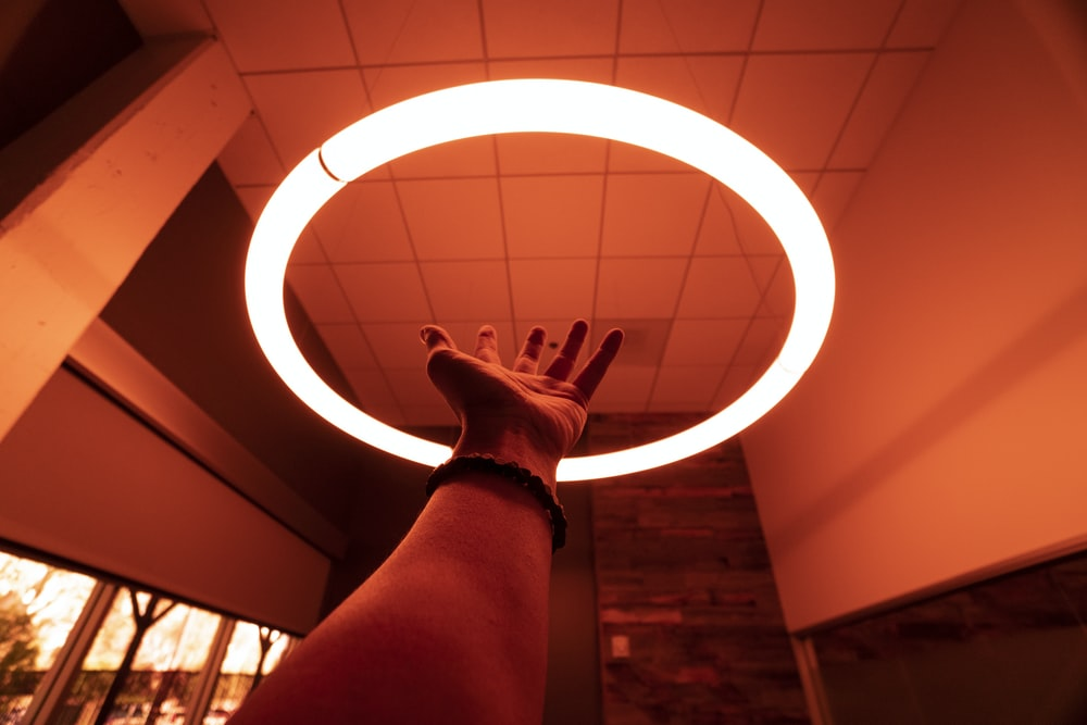 person reaching round turned-on fluorescent lamp in room