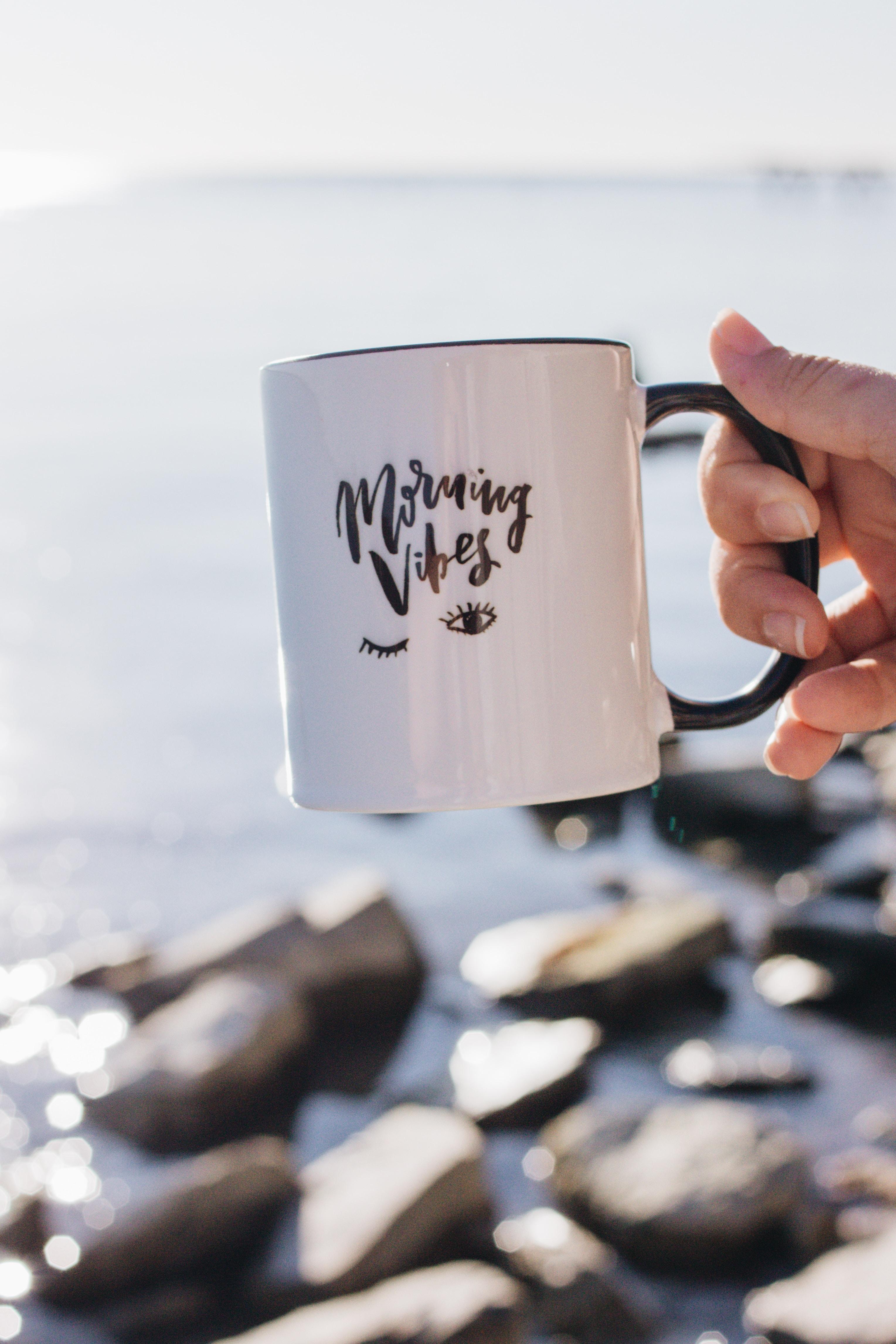 person holding white morning vibes-printed mug