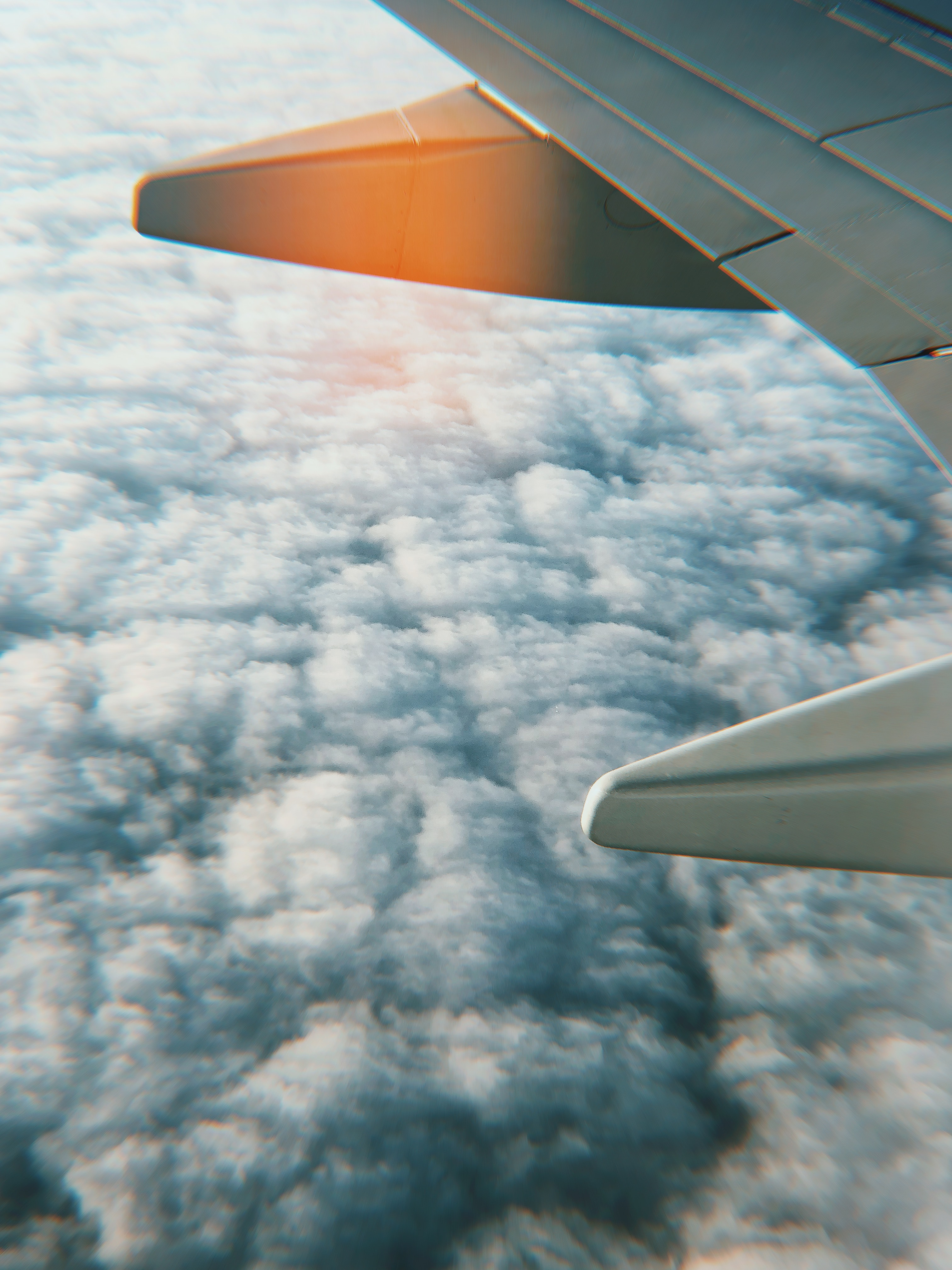 gray airplane wing above white clouds