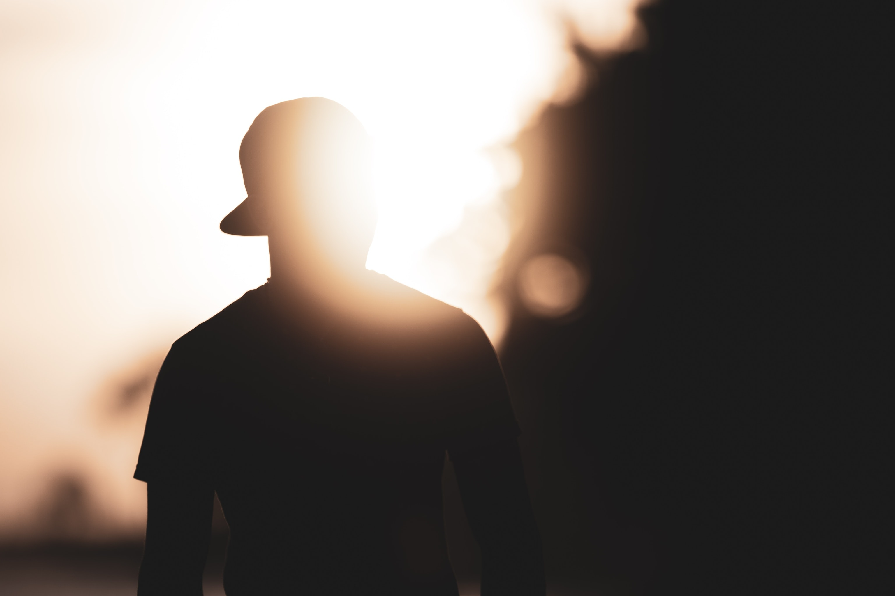 silhouette photography of person with hat