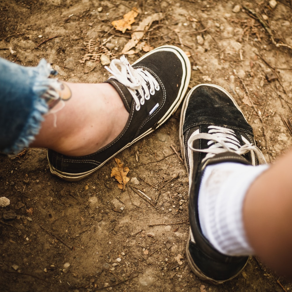 two person wearing black and white low-top sneakers