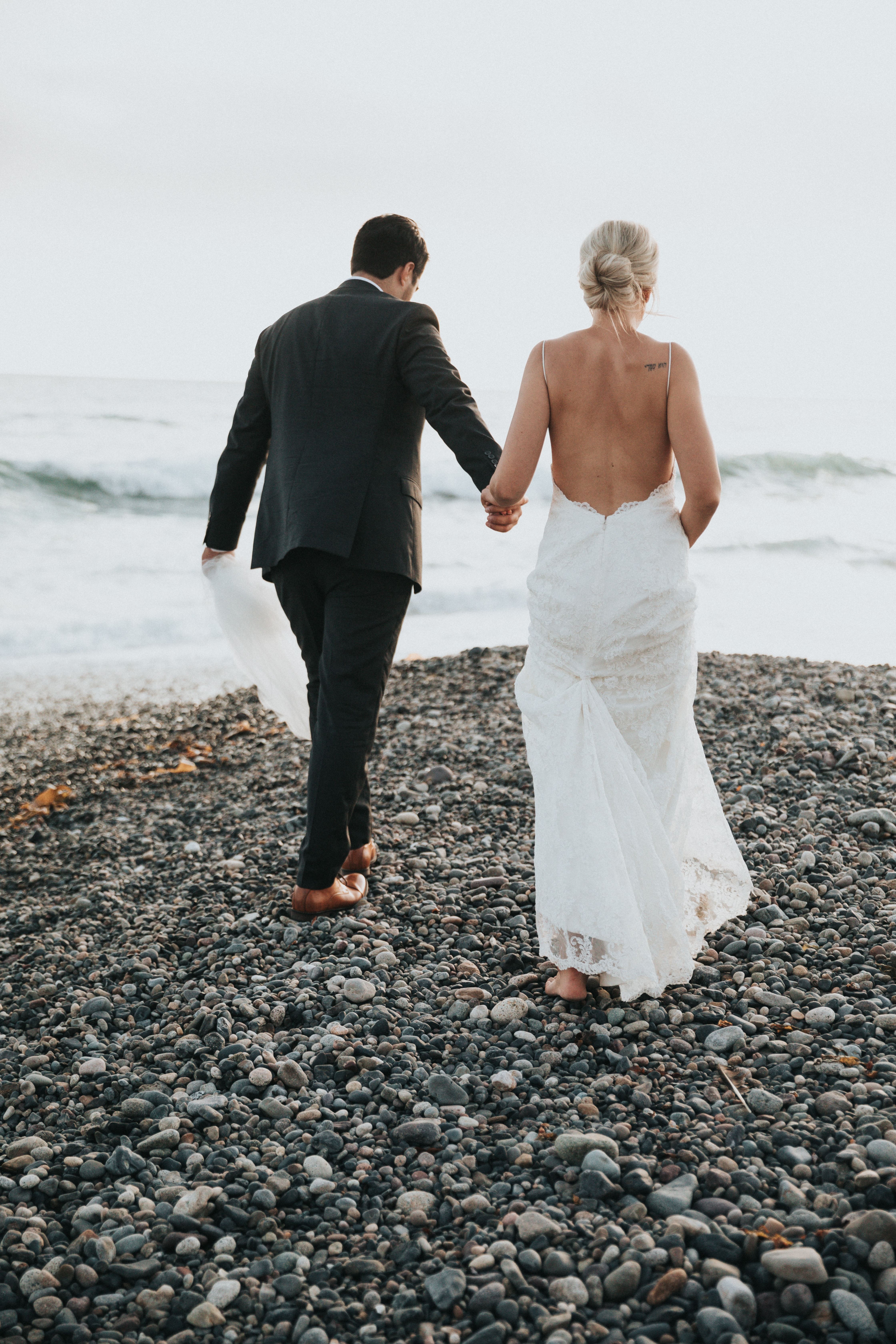 groom and bride walking on stone near body of water