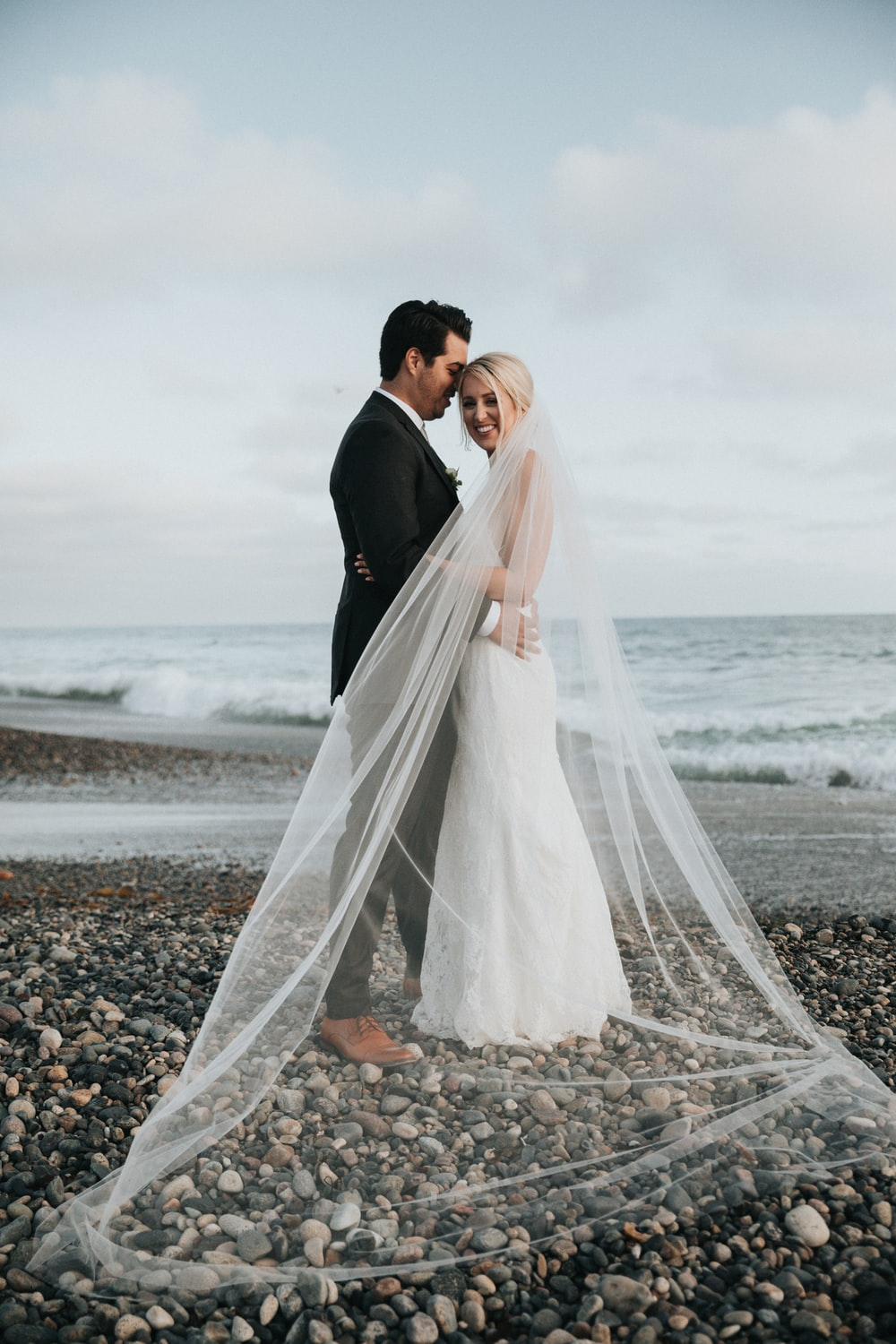 newly wedded couple standing on shore during daytime
