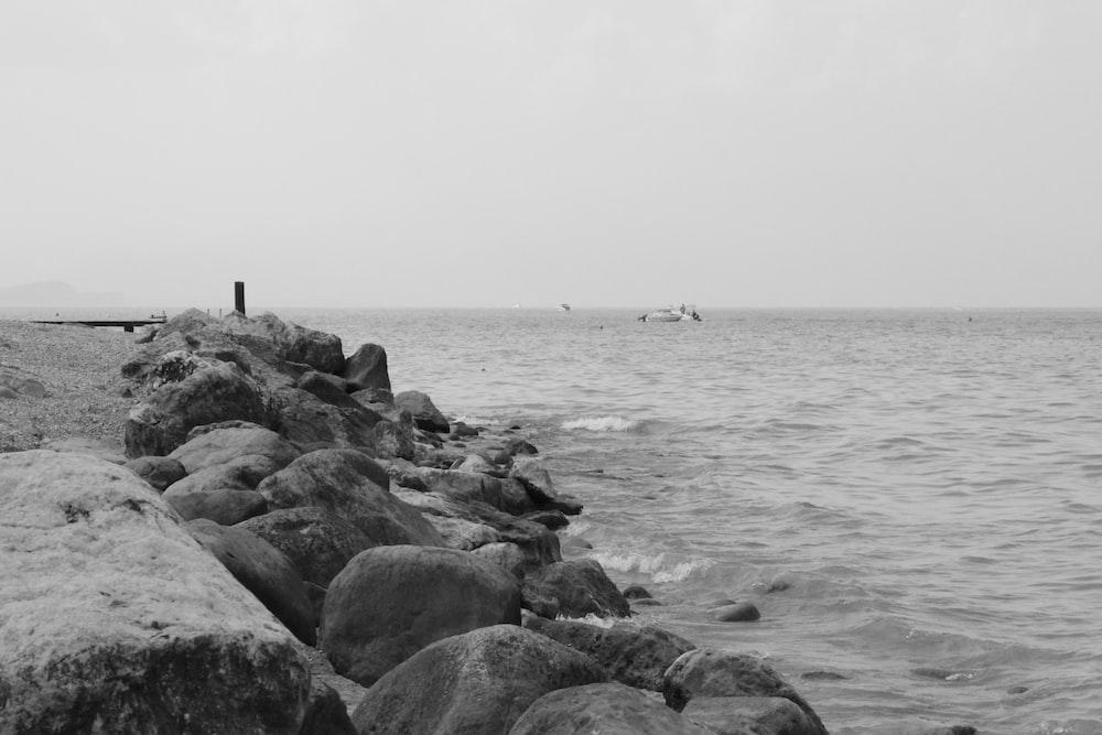 rocks near body of water grayscale photography