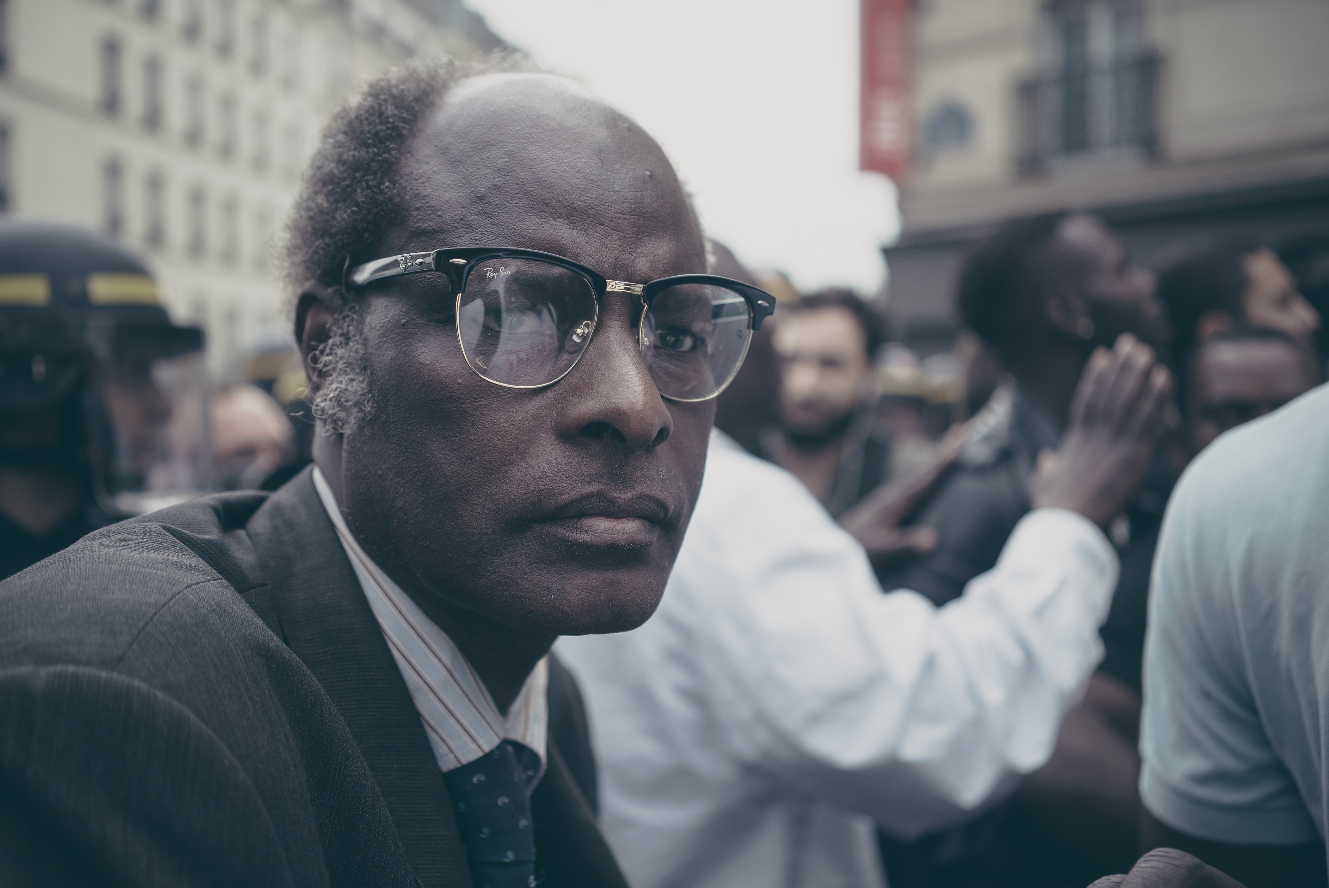 man sitting near crowd in selective focus photography