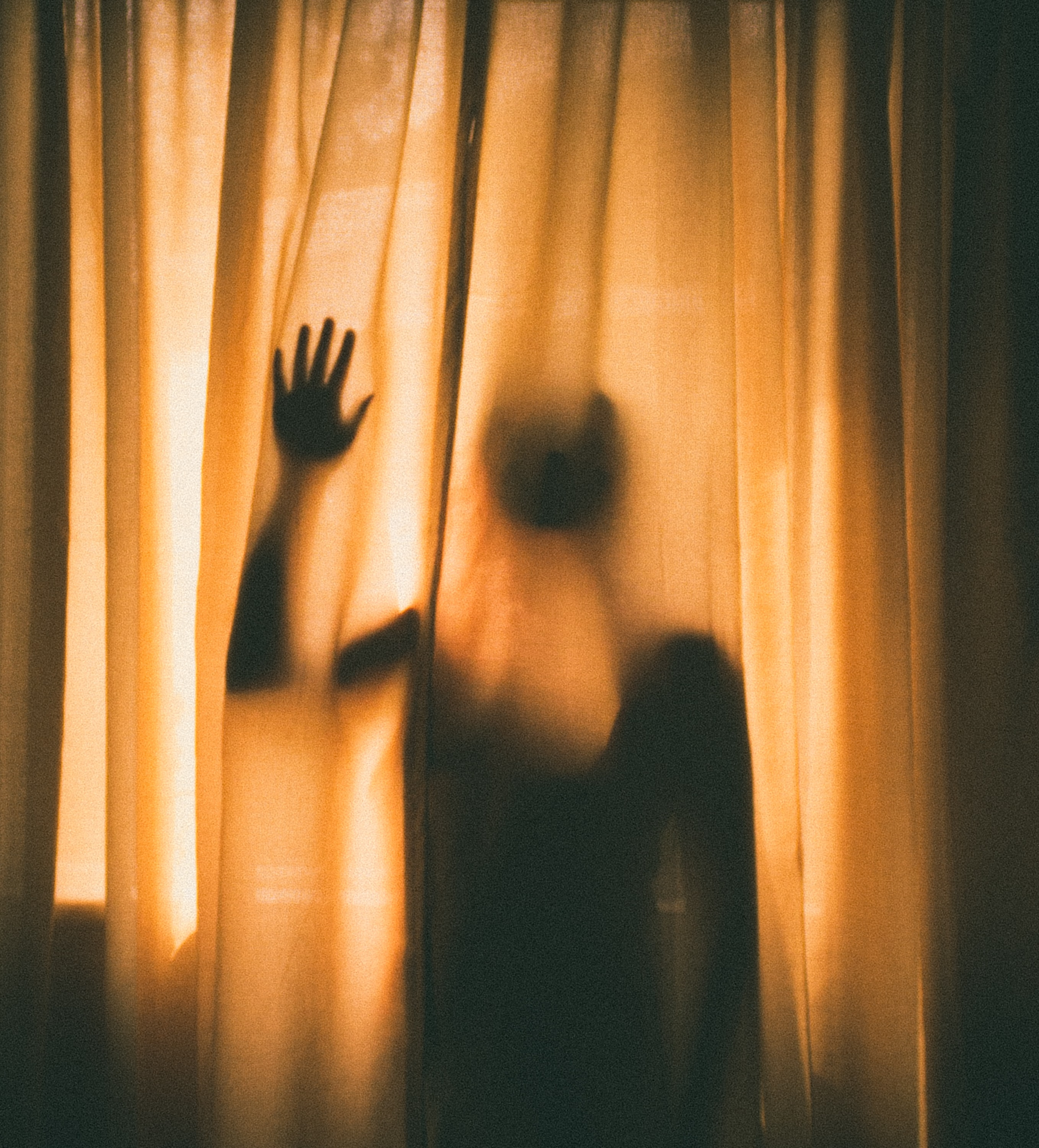 woman hiding behind of curtain