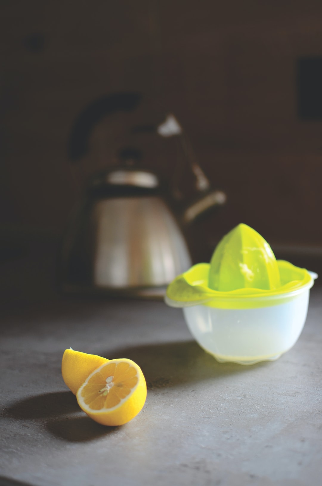 Lemons on a counter with a lemon juicer and a teapot with sun shining in through the window.