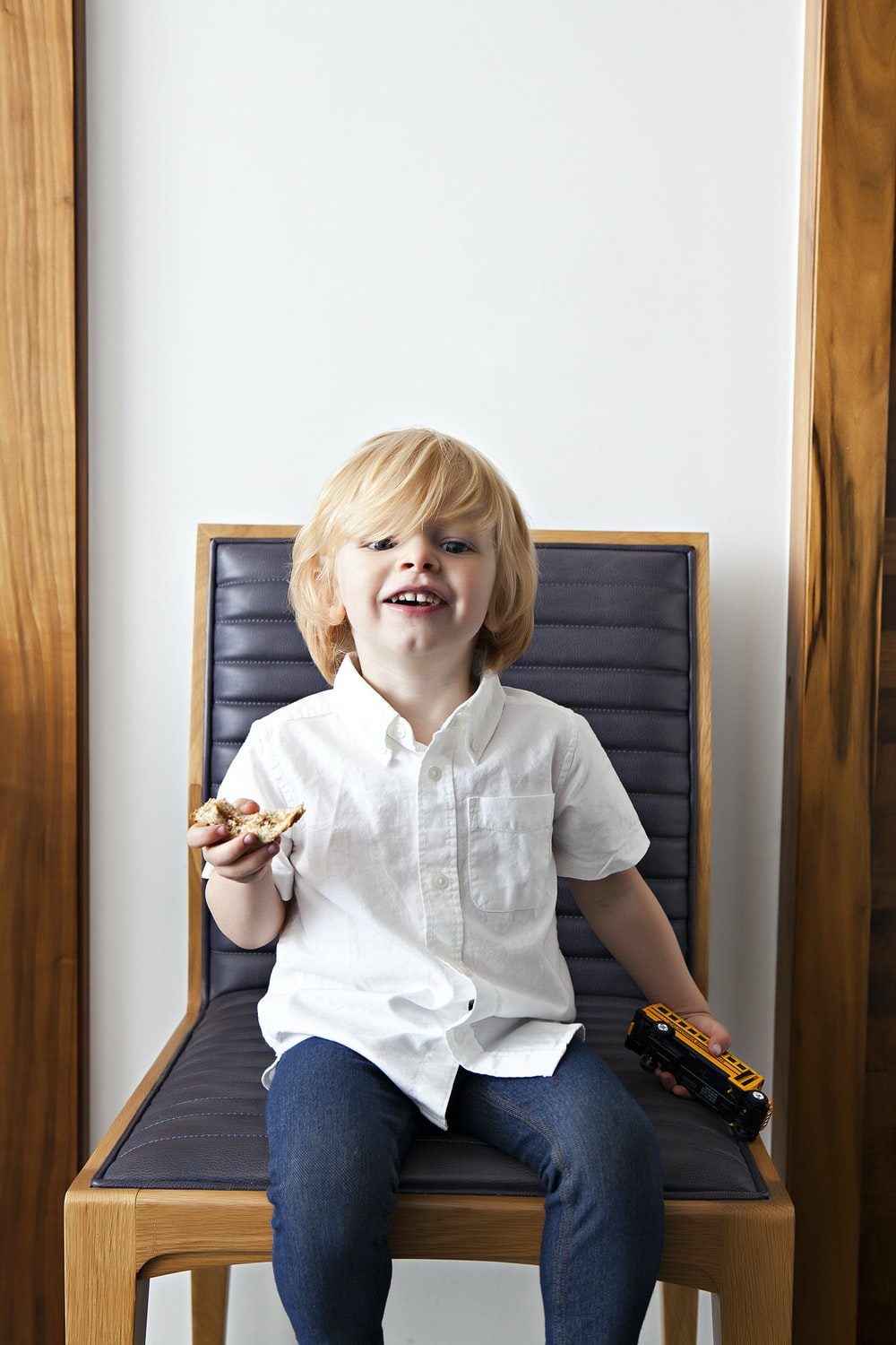 boy sitting on black padded chair