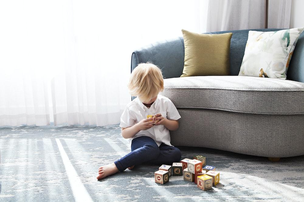 boy sitting on floor playing blocks near couch