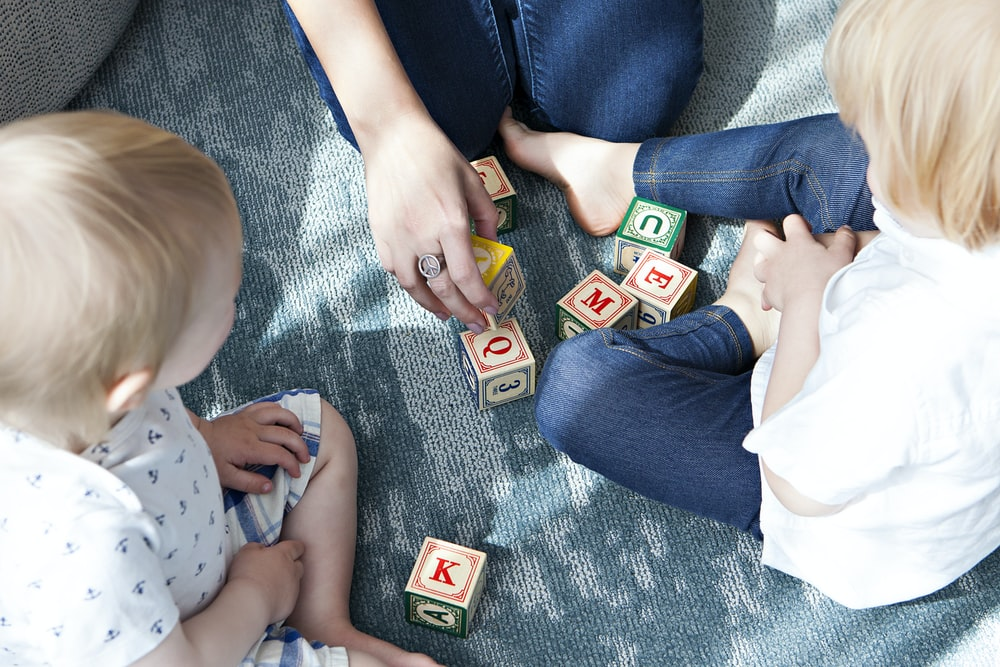 two toddler playing letter cubes