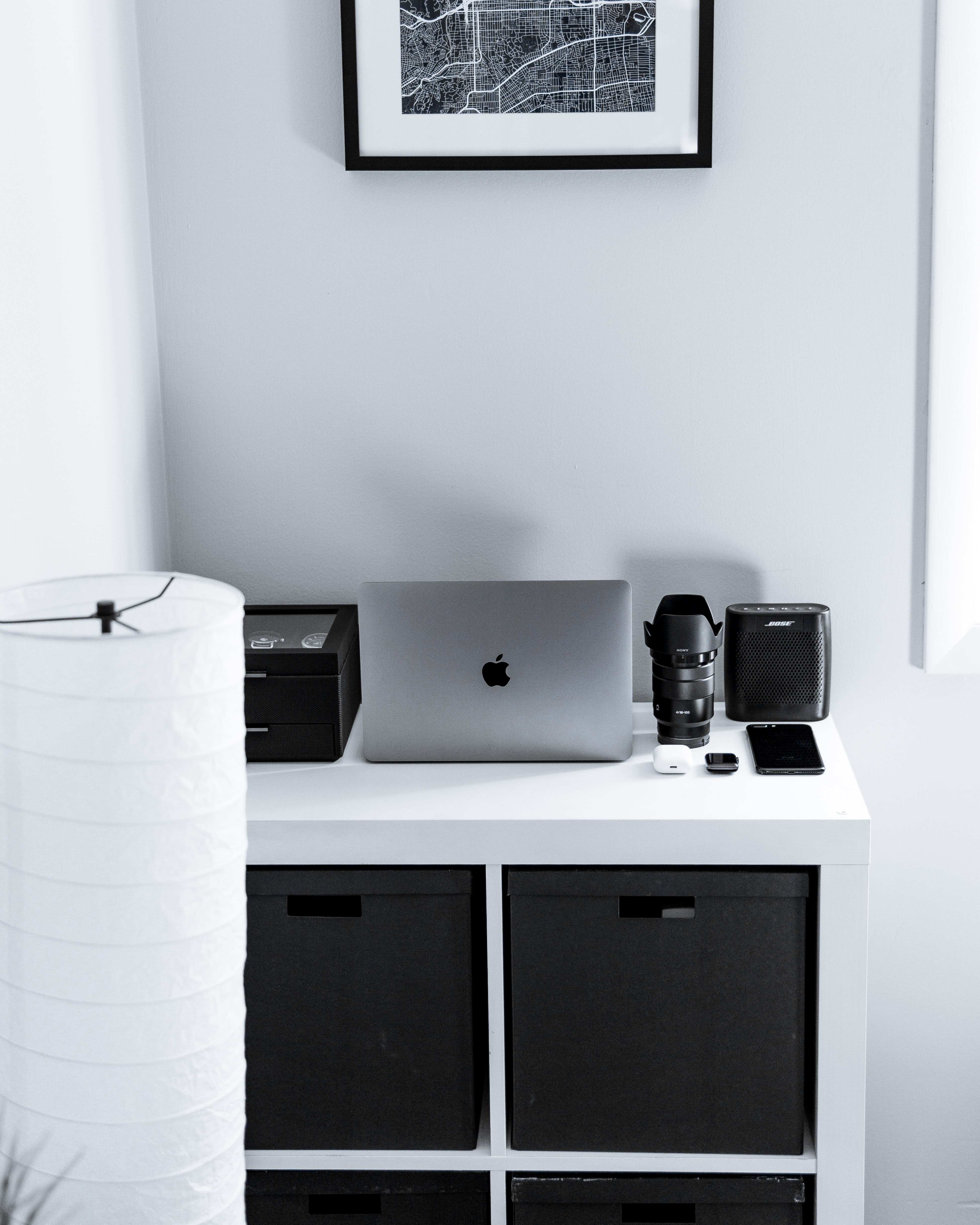 silver MacBook beside black camera lens and speaker on dresser