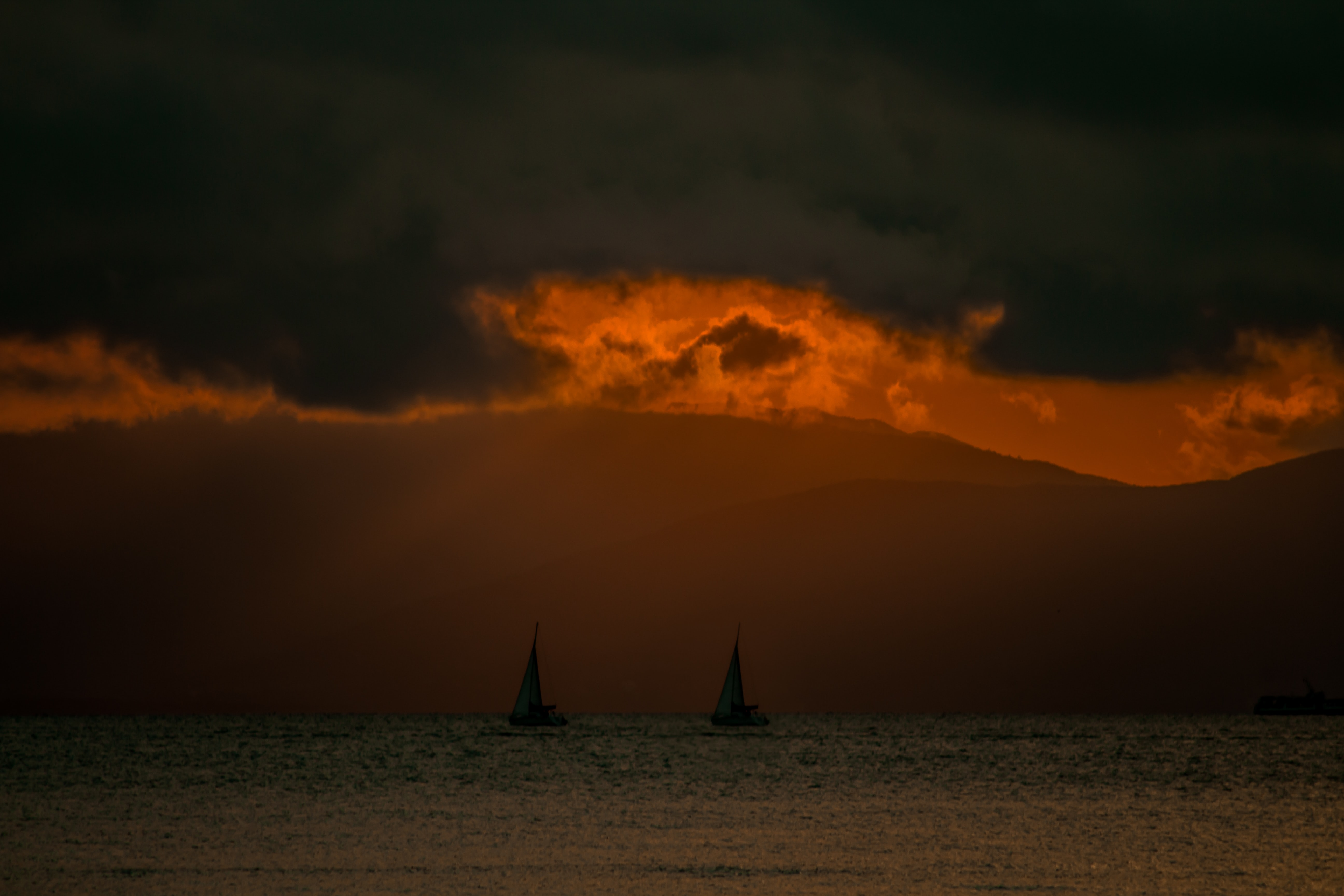 two silhouette of sail boats