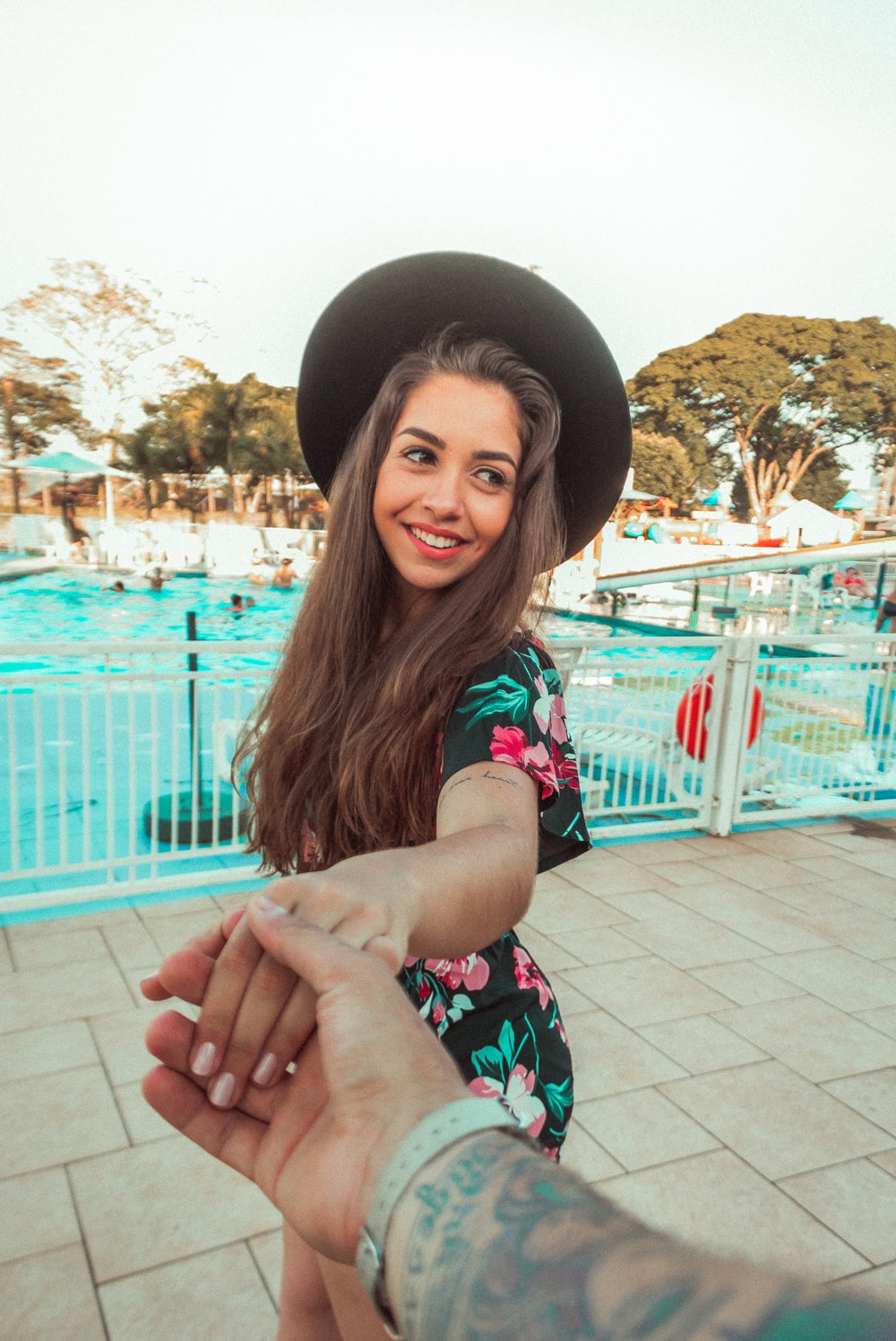 woman standing and smiling while holding hands of another person near swimming pool