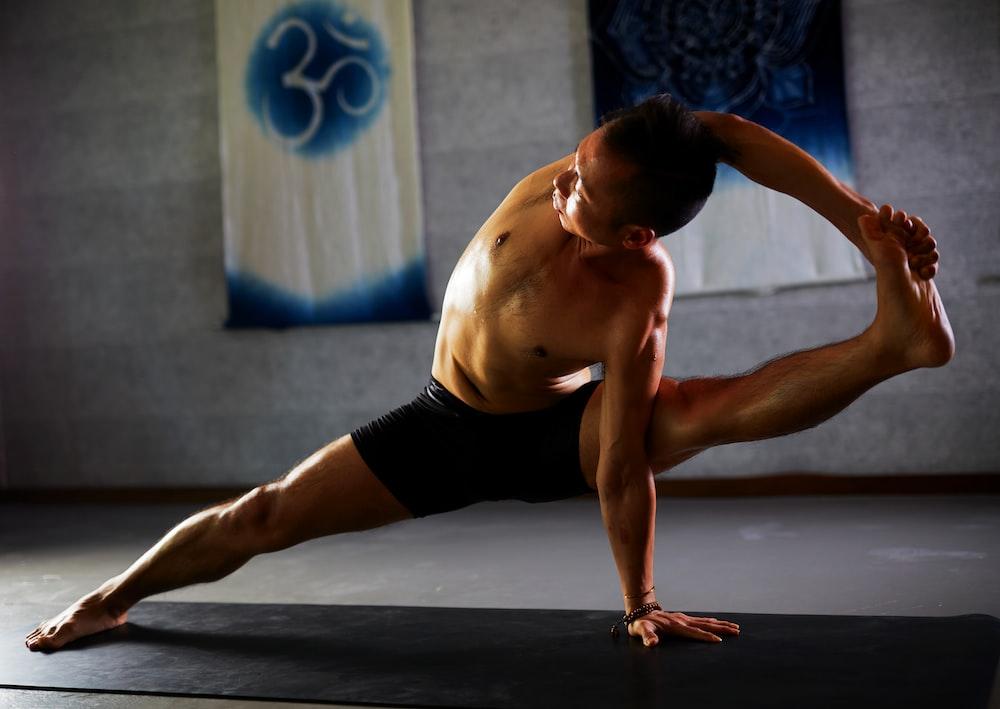 man stretching on black mat