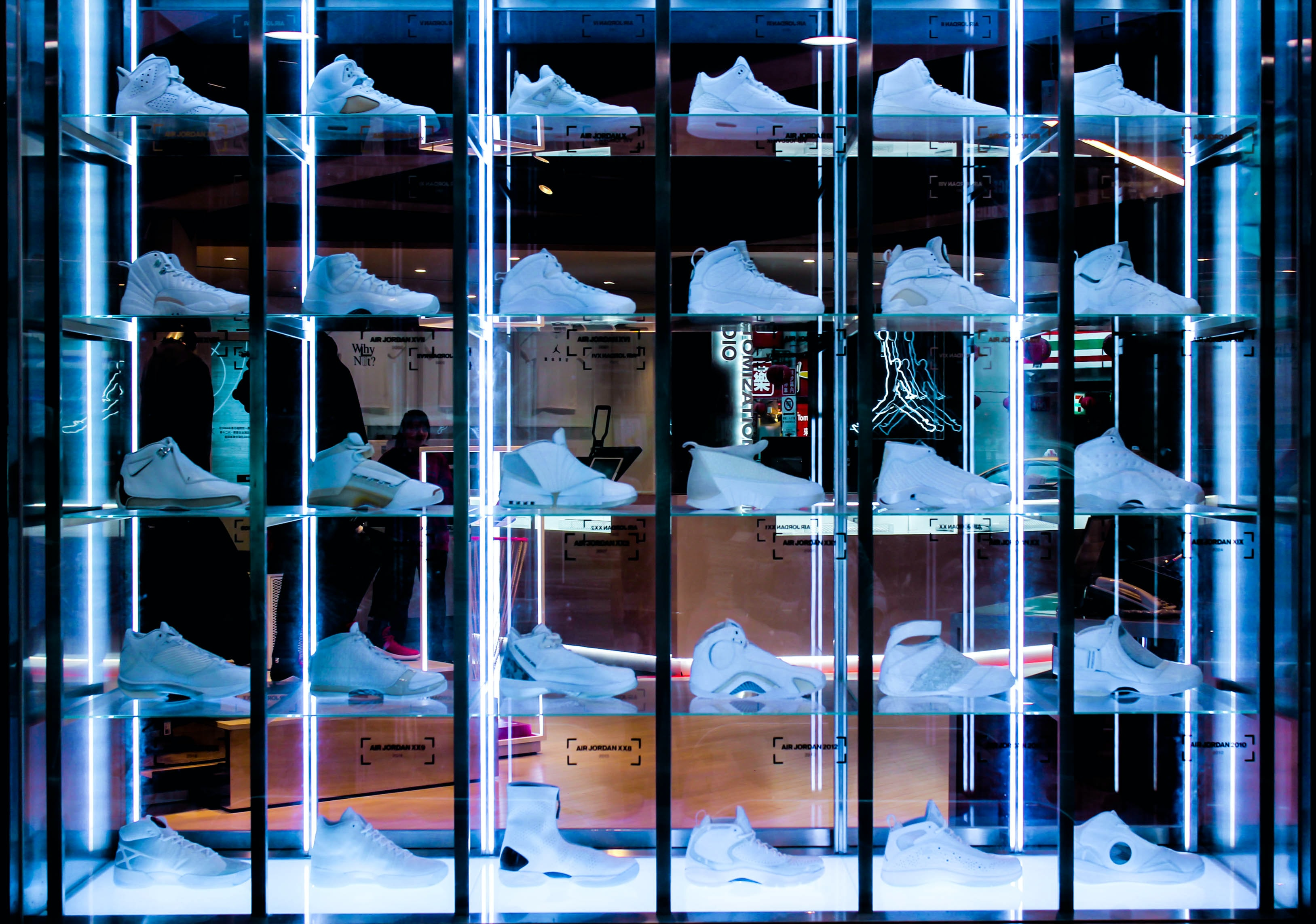 white sneaker collection on glass rack