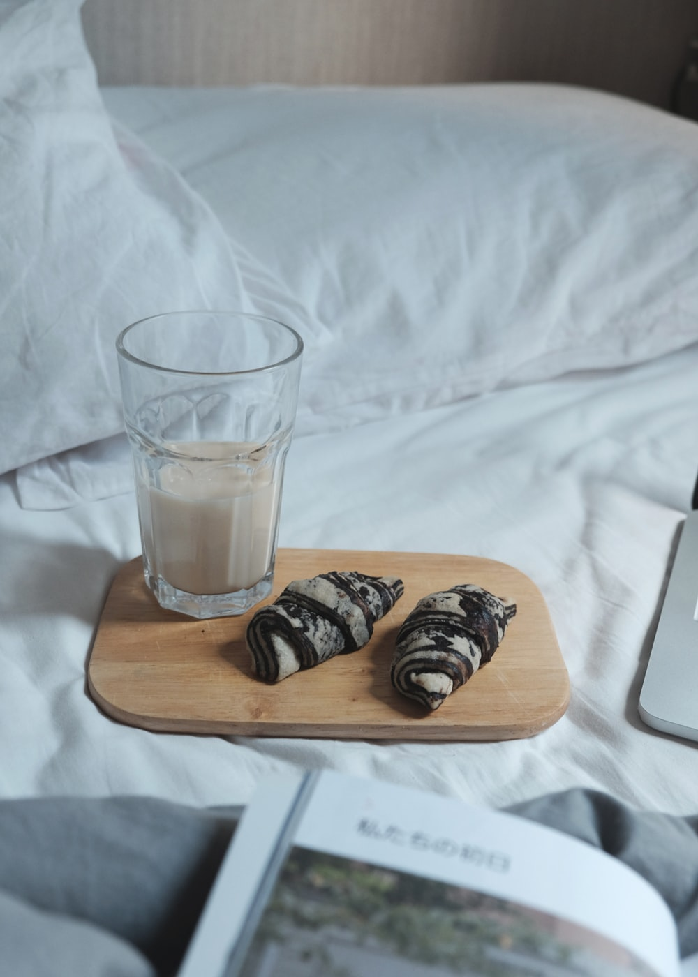 drinking glass filled with white liquid served on wooden board
