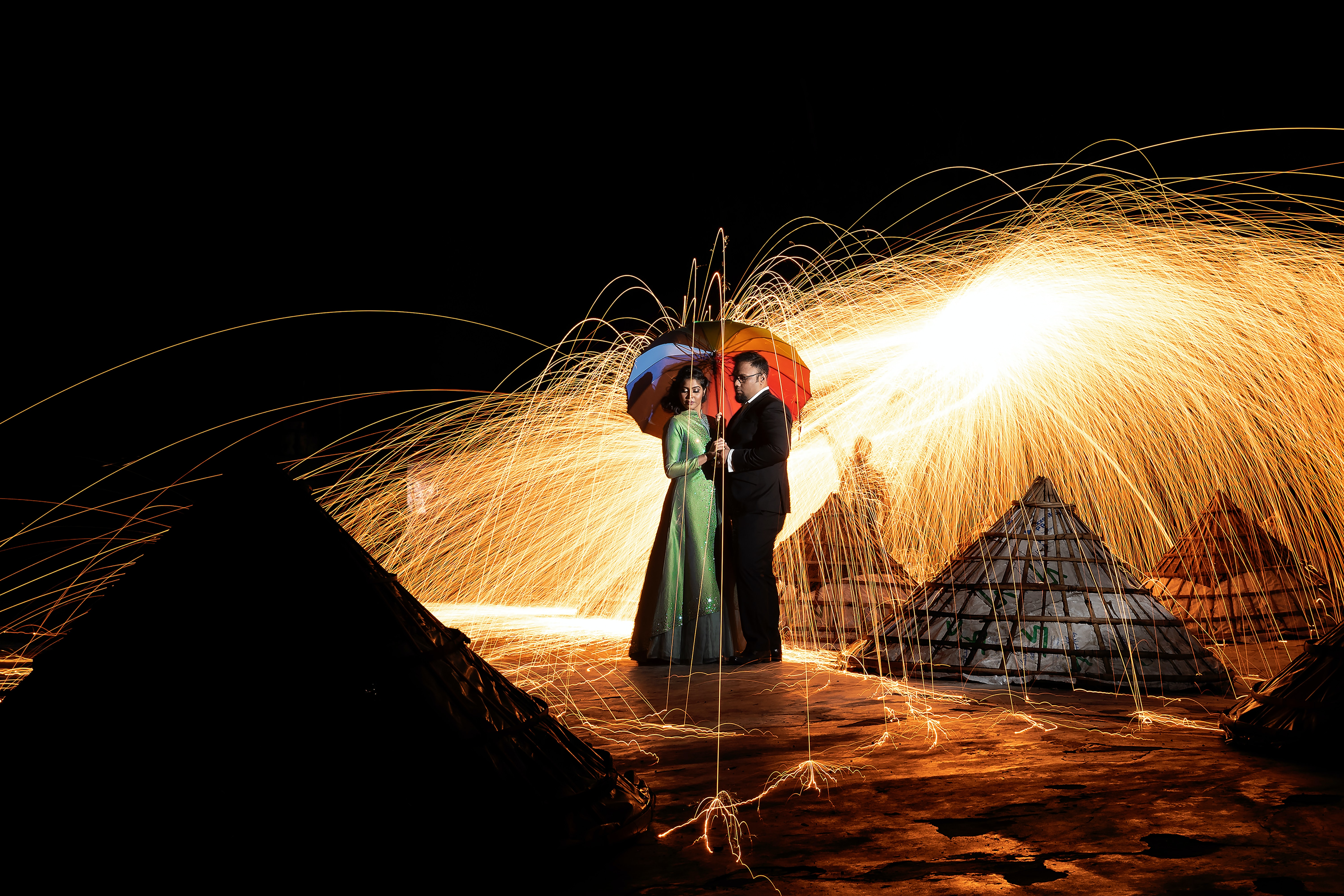 man and woman standing near huts steel wool photography