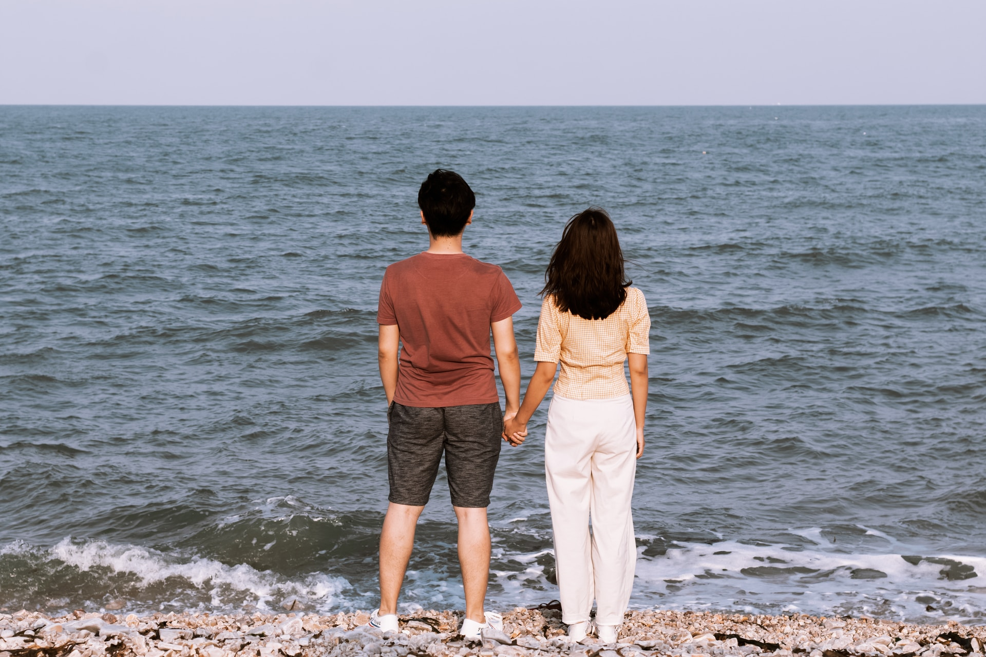 man and woman standing infront of ocean water at daytime
