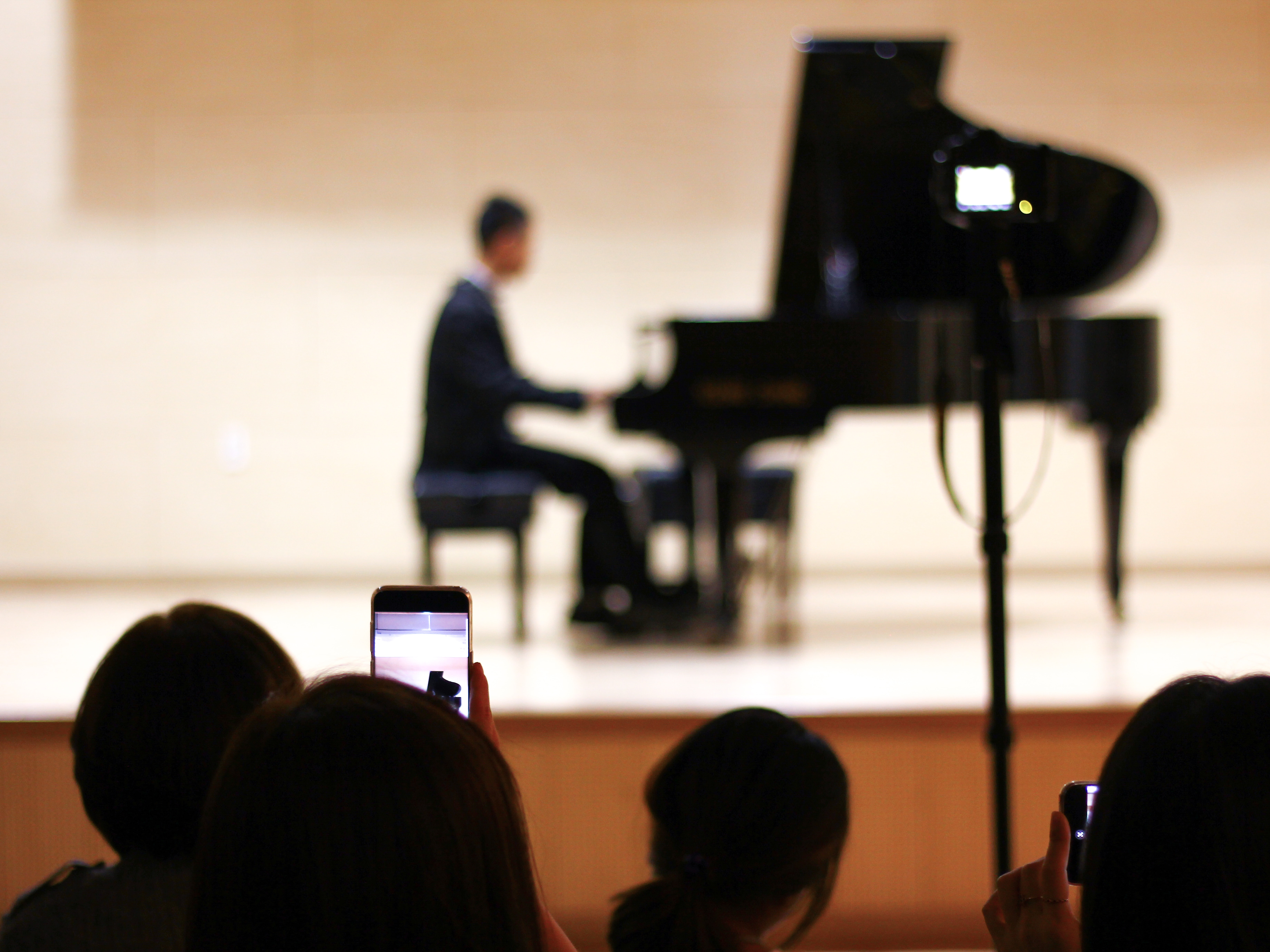person taking photo of person playing piano on stage