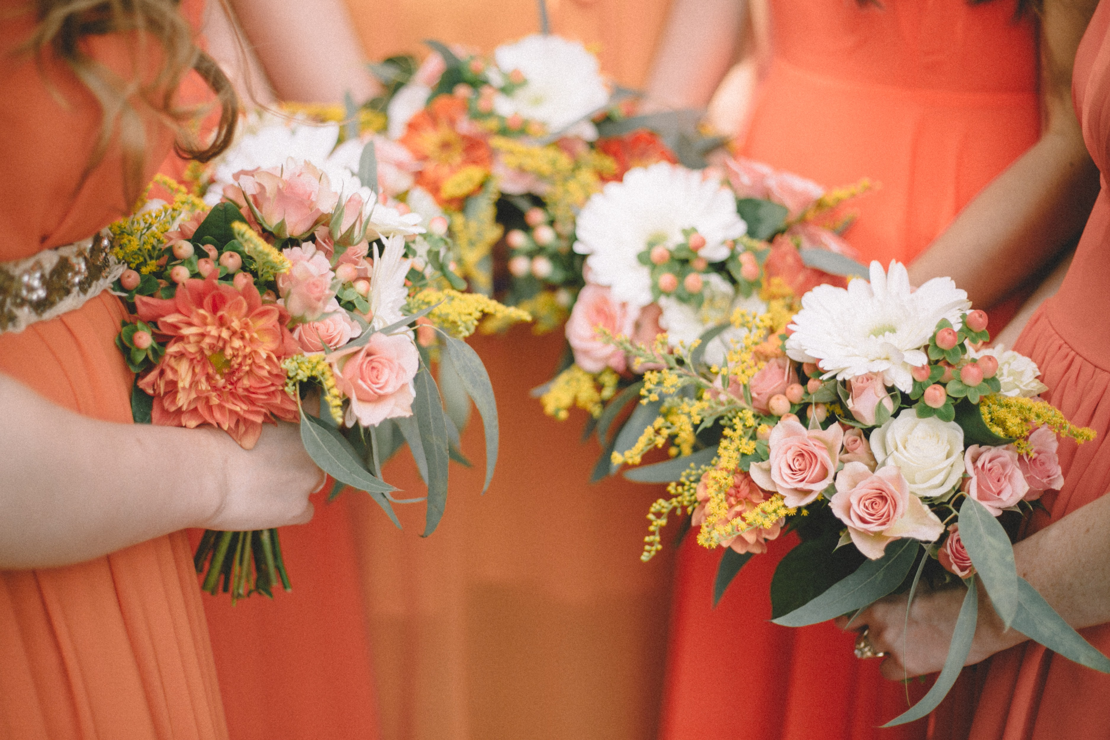 four women holding bouquet of flowers