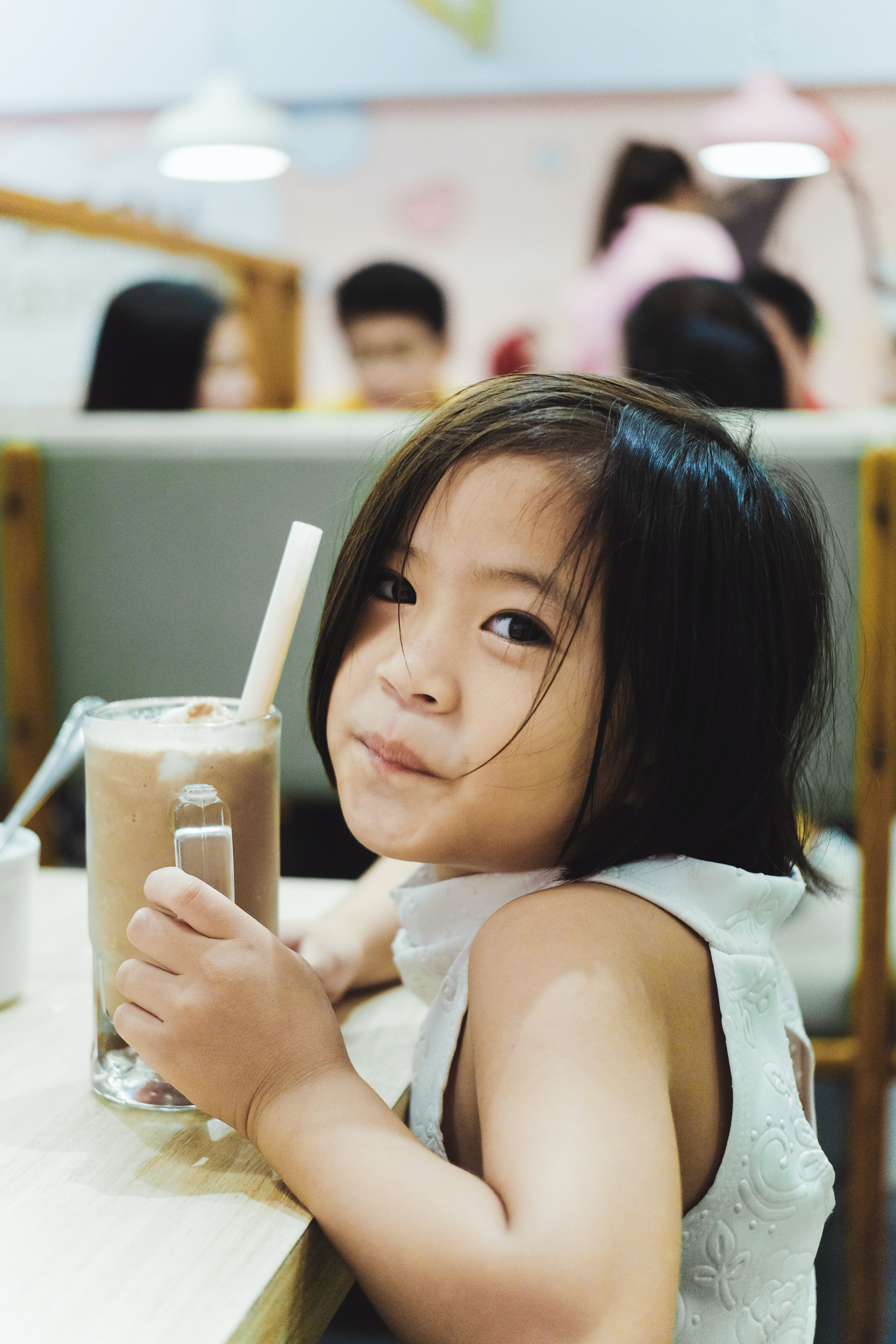 girl holding cup filled with black liquid