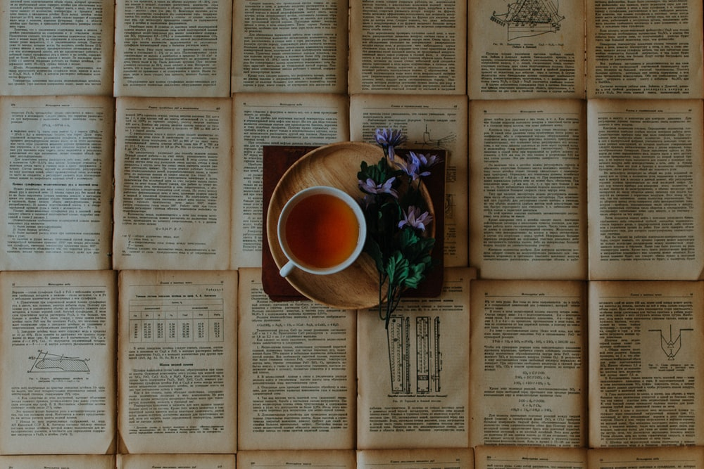 cup of coffee beside purple flowers on top of book