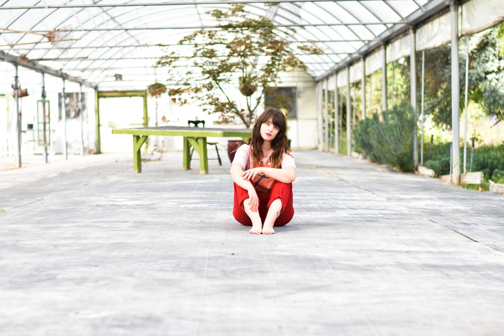 woman sitting on gray concrete surface posing for photo