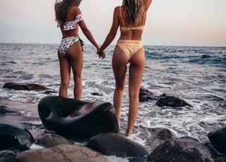 two women standing on rock while raising their hands near sea during daytime