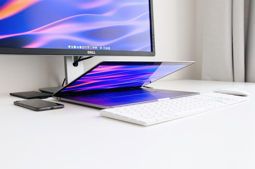 turned-on Dell monitor at table in front of laptop, keyboard, and mouse