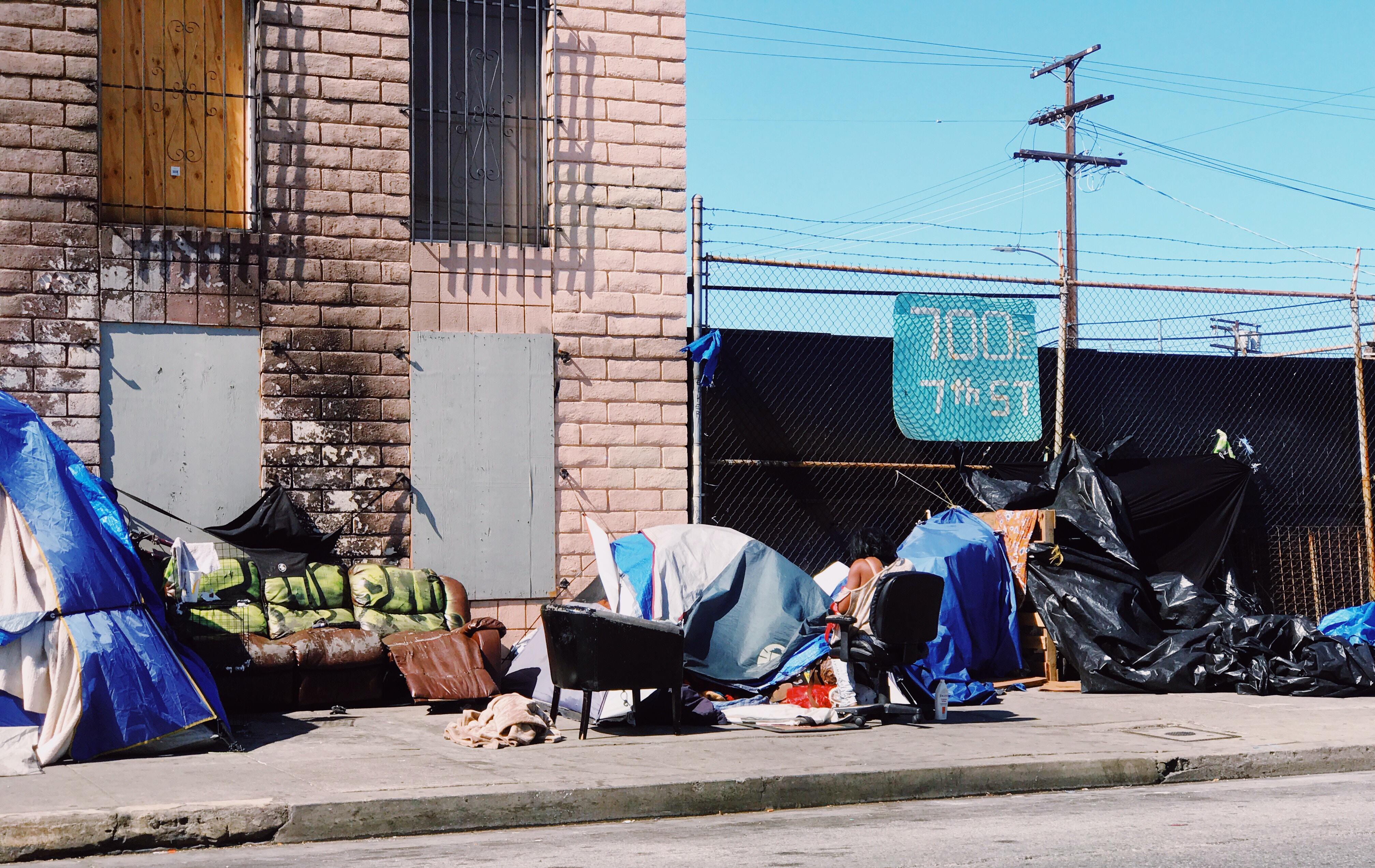 blue tarps beside brown concrete building