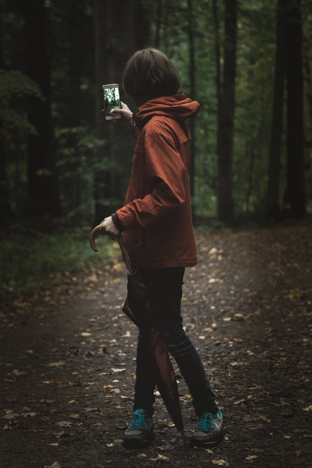 woman wearing red hoodie holding smartphone near green leafed tree