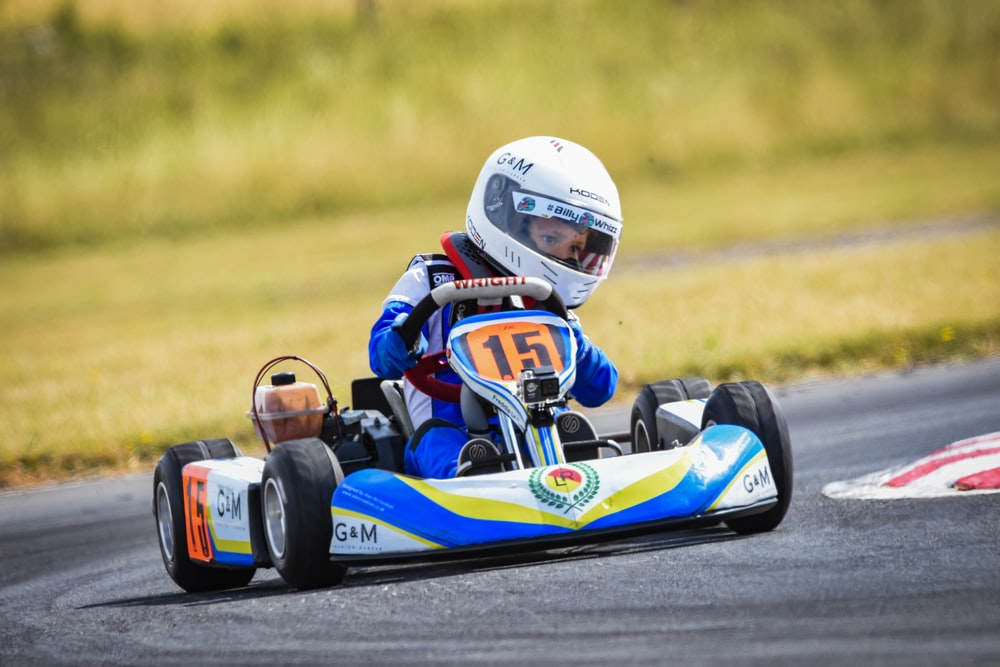 shallow focus photography of boy riding go-kart
