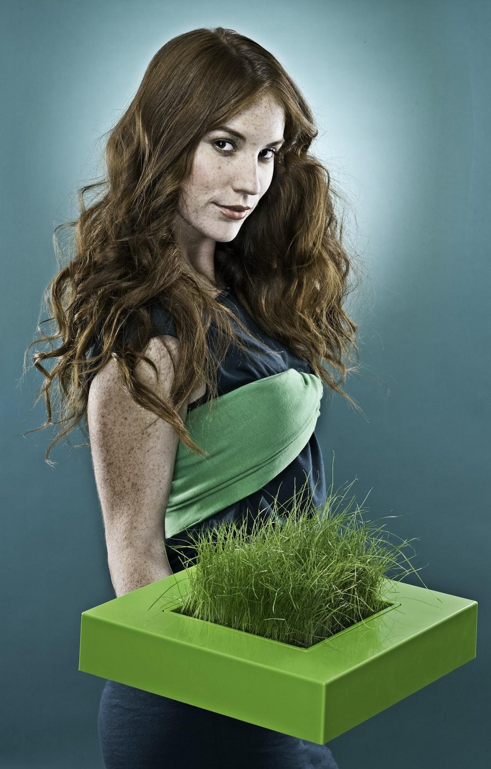 woman holding green grass